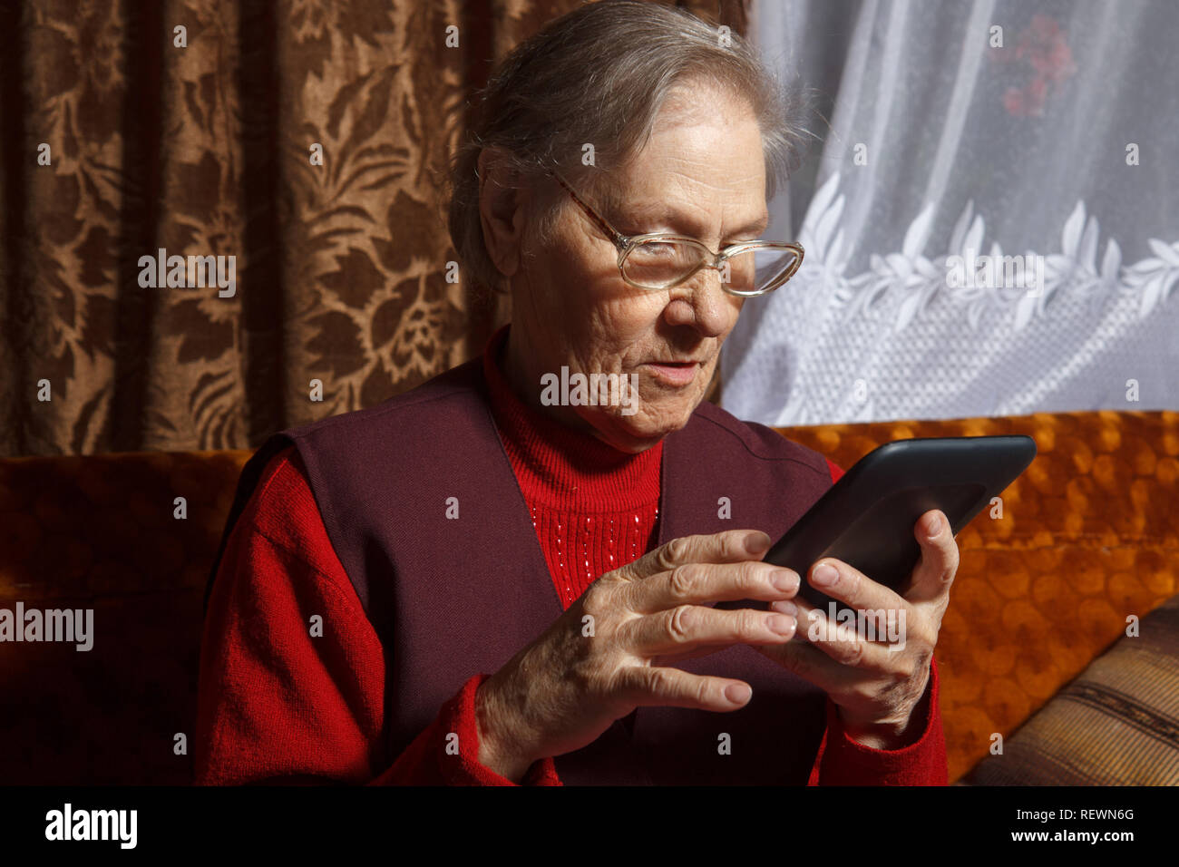 old woman using ebook reader - Stock Image