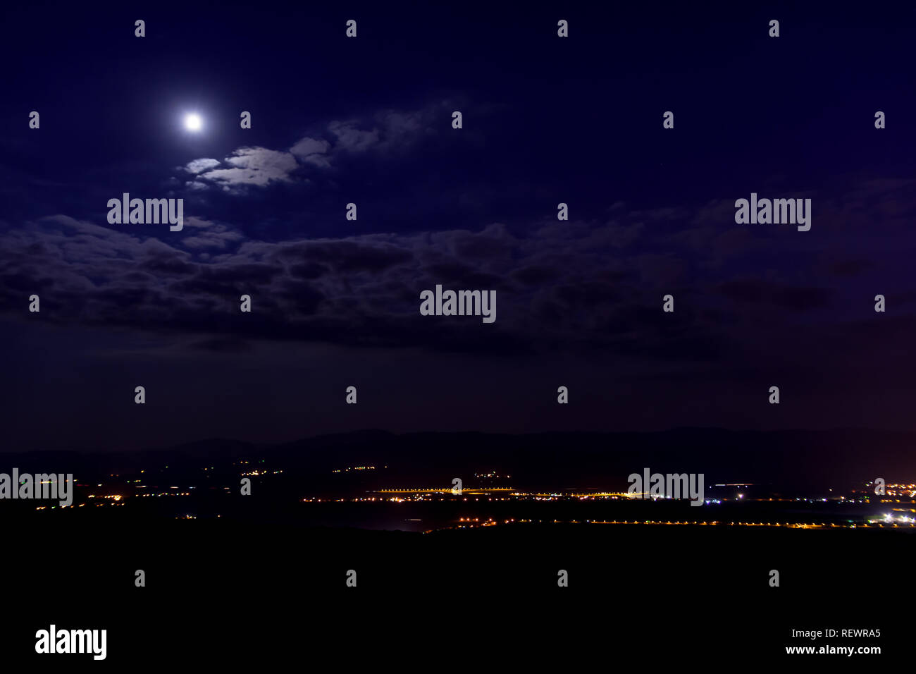 Night cityscape of town Pirot in Serbia. Moon that illuminates blue almost violet clouds, street lights can be seen at the base of the city. - Stock Image