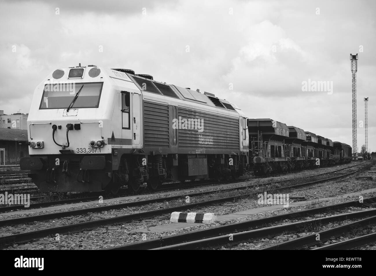Beautiful old spanish train parked at railway station. The gray scale shot shows a powerful locomotive damaged with its wagons. Estremadura. - Stock Image