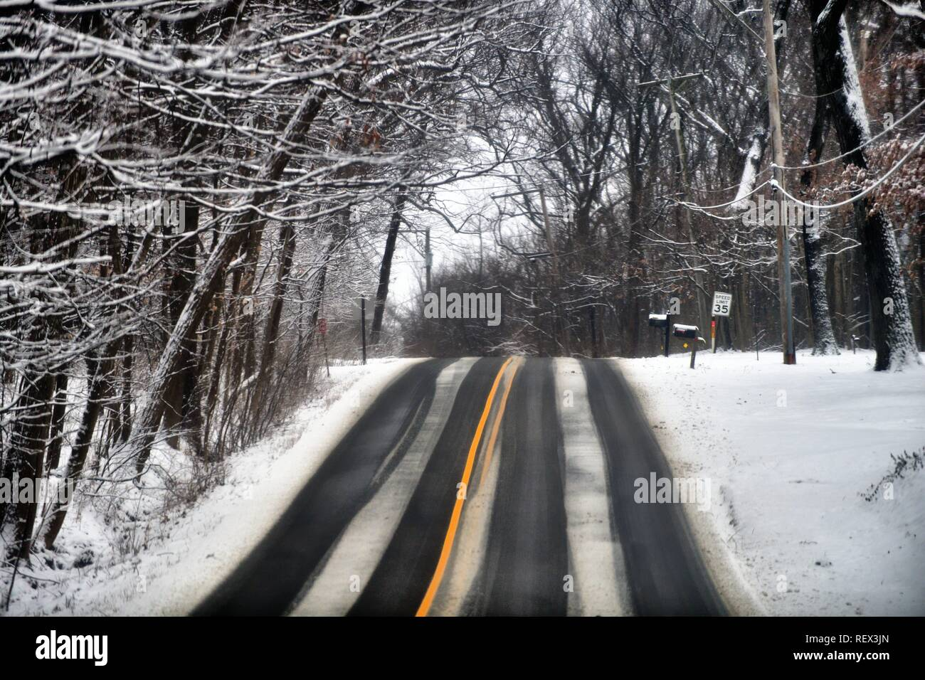 Wayne, Illinois, USA. A country highway during a snow shows evidence of slippery conditions as it crests the top of a hill. - Stock Image