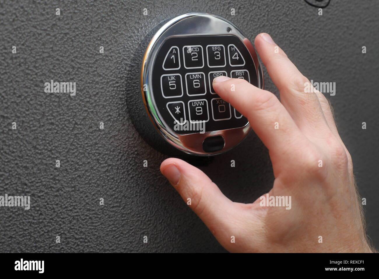 Hands entering combination to open digital lock on safe