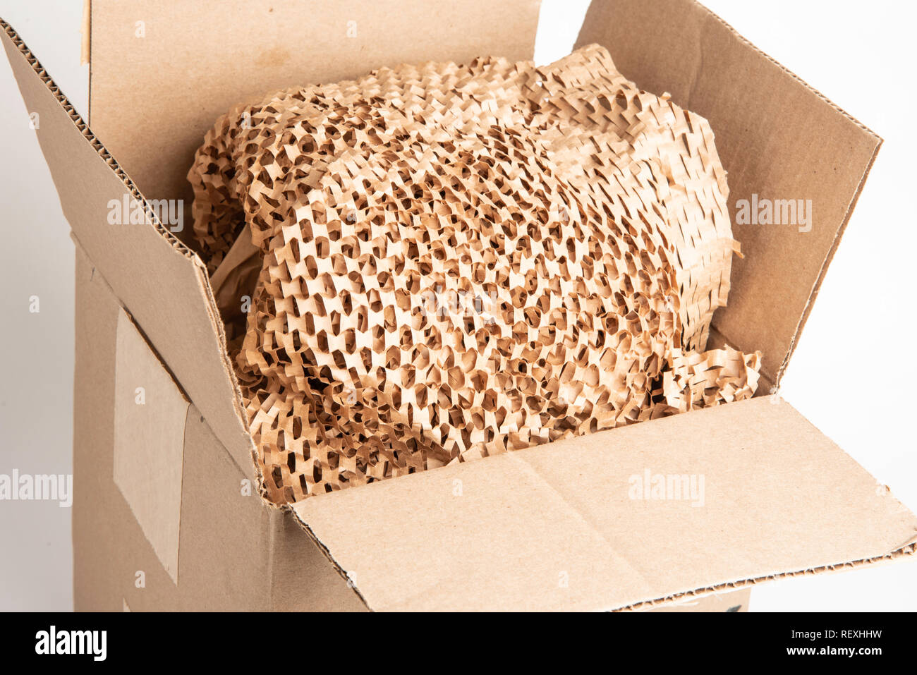 A bunched recyclable perforated brown paper filler on top of an opened box package. - Stock Image