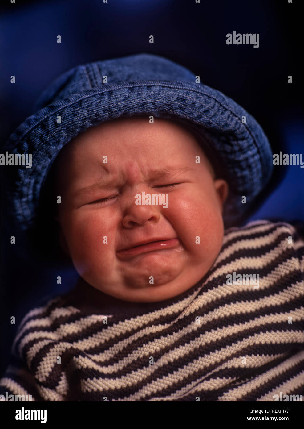 A closeup of an upset and crying child's face wearing a hat - Stock Image