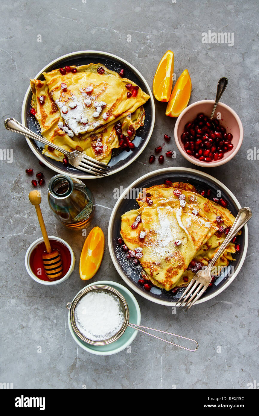 Flat-lay of sweet crepes topped with pomegranate. Thin pancakes, fruits, honey and maple syrup - Stock Image