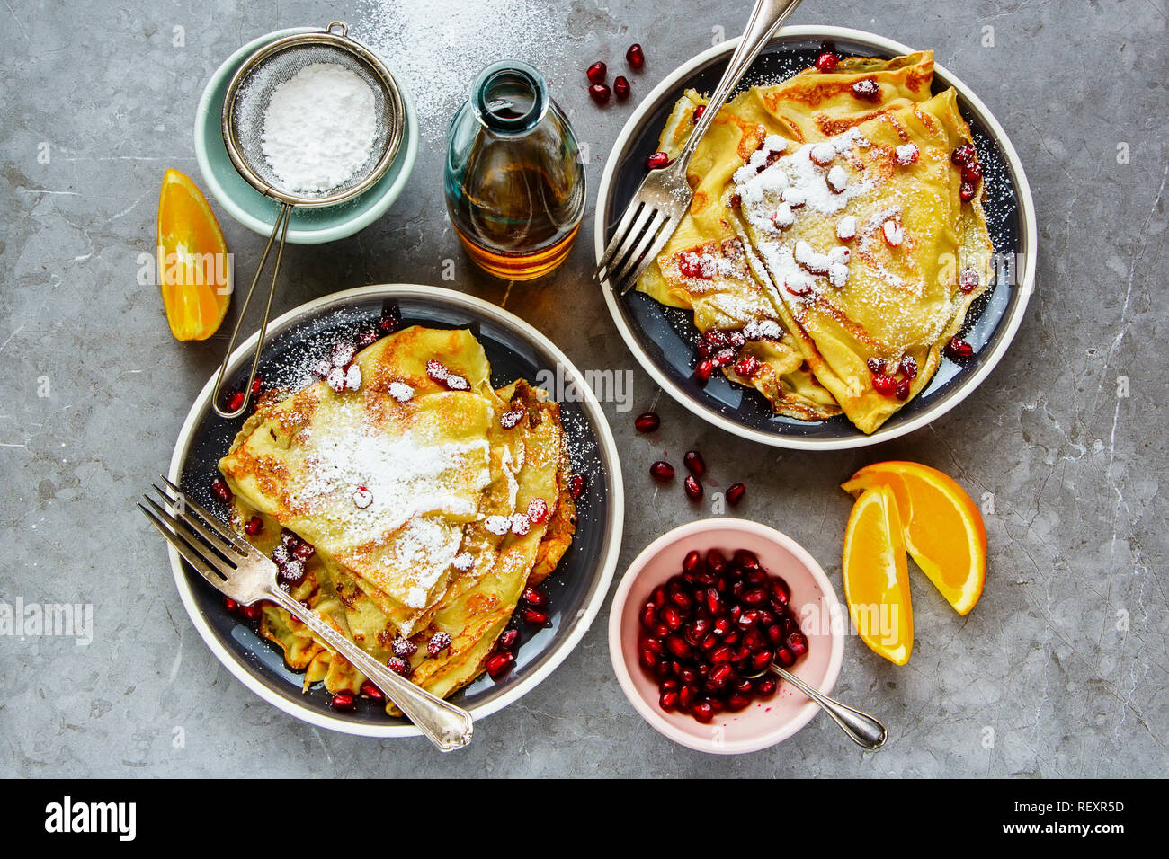 Sweet crepes topped with pomegranate and sugar. Thin pancakes, fruits and maple syrup flat-lay - Stock Image
