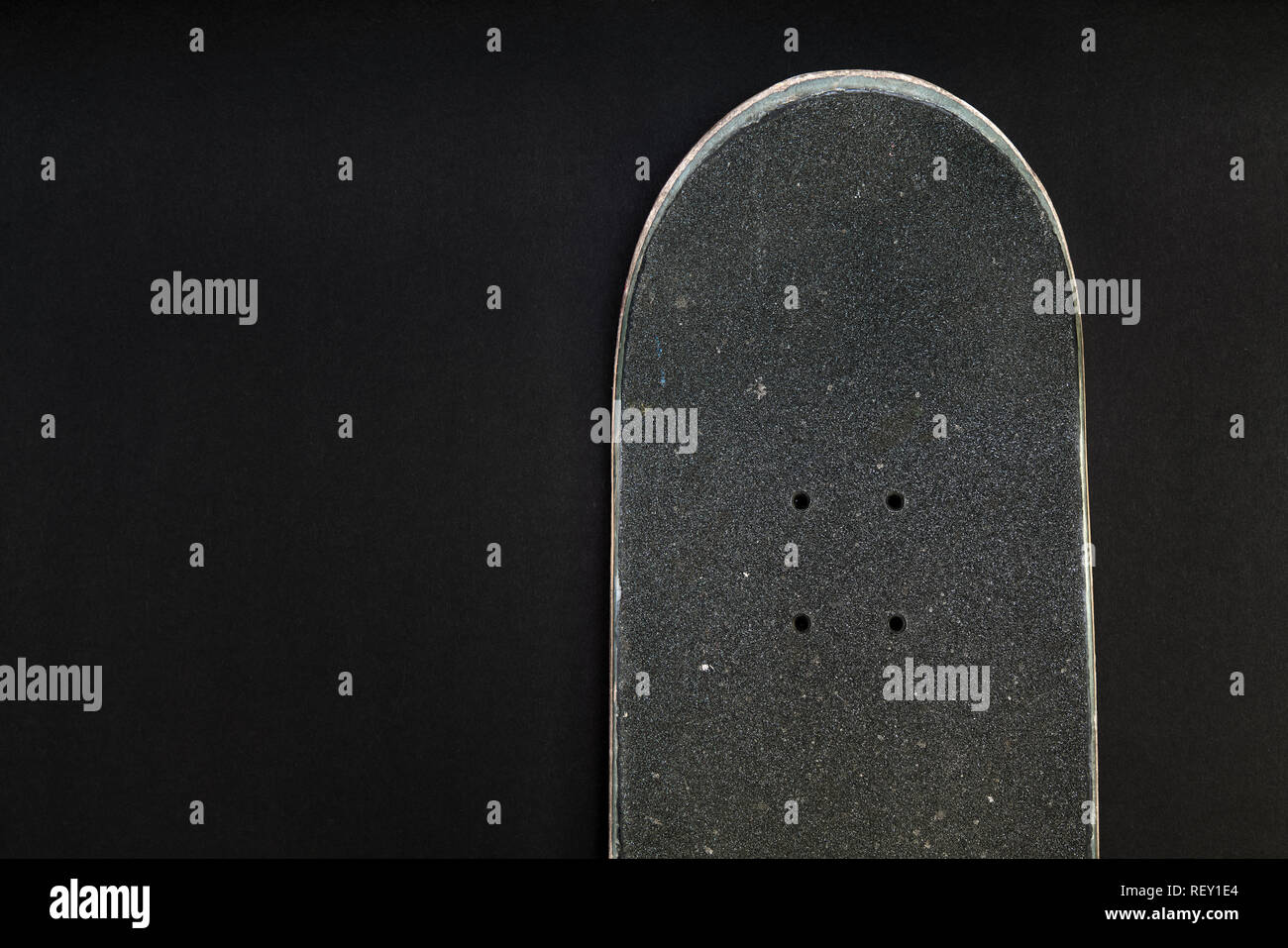 9bca9c0a Front top of a skateboard deck with grip tape and bolt holes on black  background -