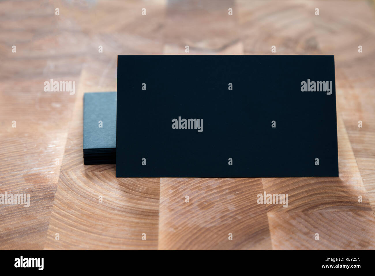Photo of black blank business cards on wooden background. Template for ID. Top view - Stock Image