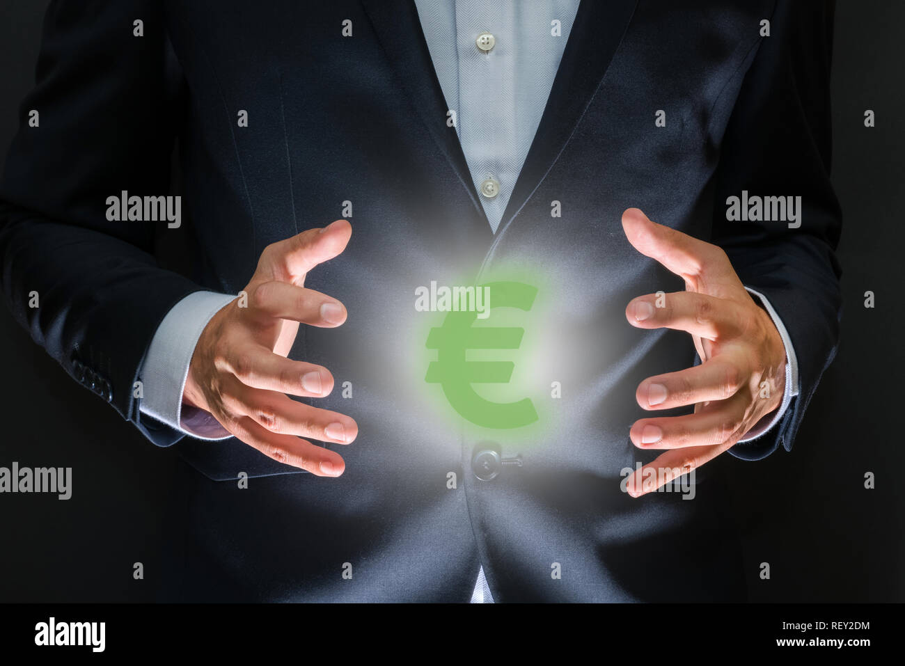 Controlling money concept. Currency symbol - euro sign between human hands. Money making and wealth - Stock Image