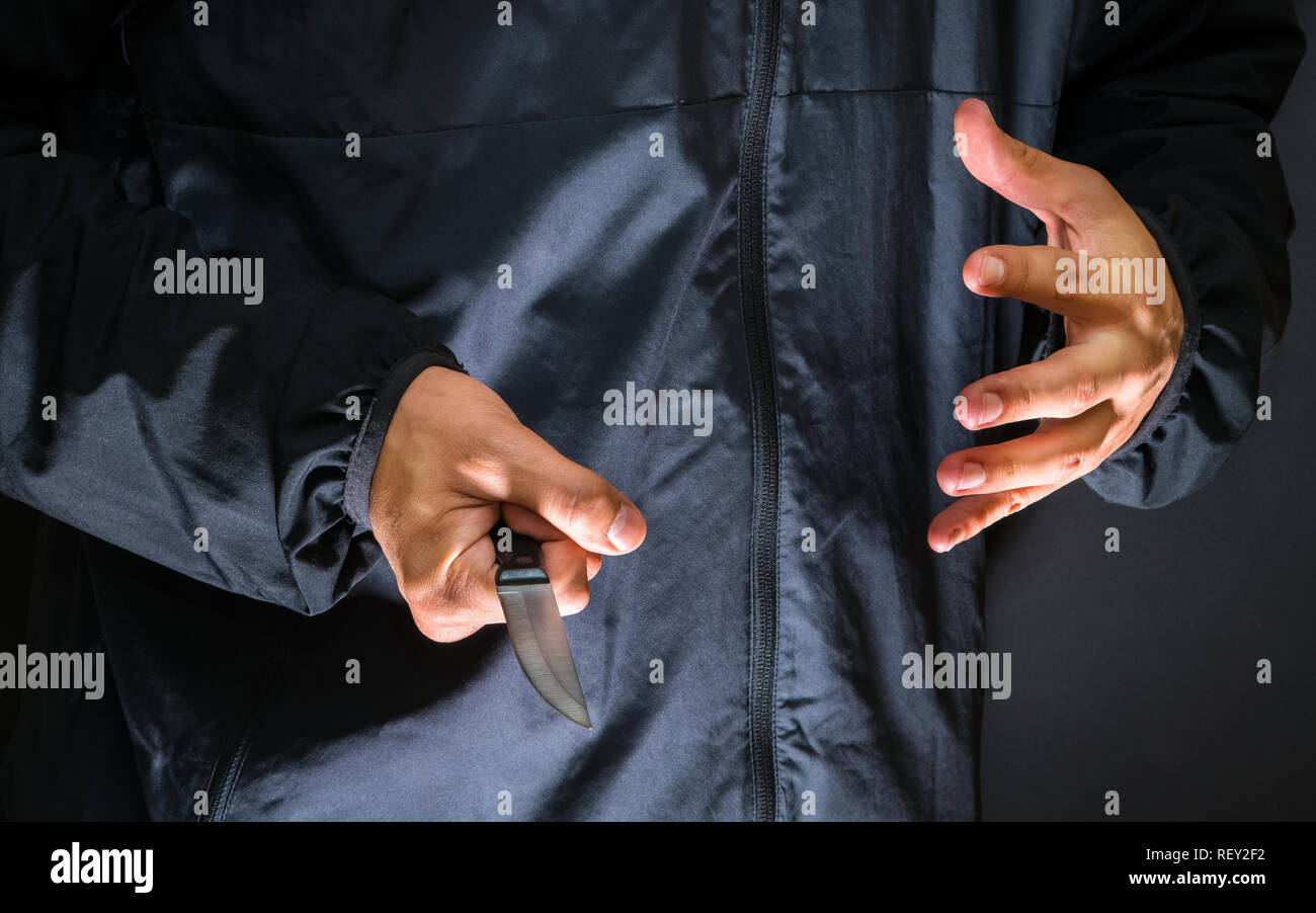 Street robber with a knife - killer person with sharp knife about to commit a homicide, murder scenery - Stock Image