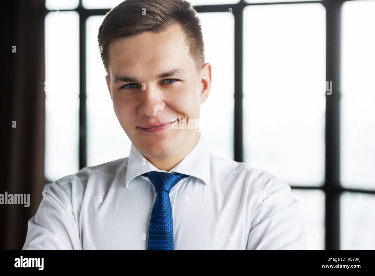 Portrait of confident young business man looking at camera. - Stock Image