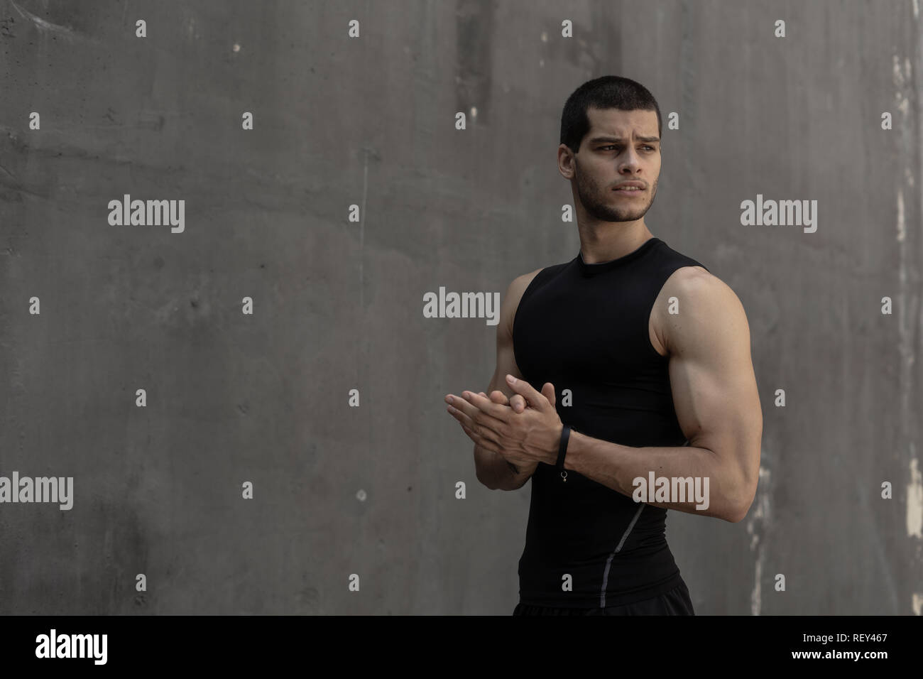 Portrait of handsome, attractive strong fashionable sporty sportive muscular brave, powerful man tapping hands on gray urban wall background - Stock Image