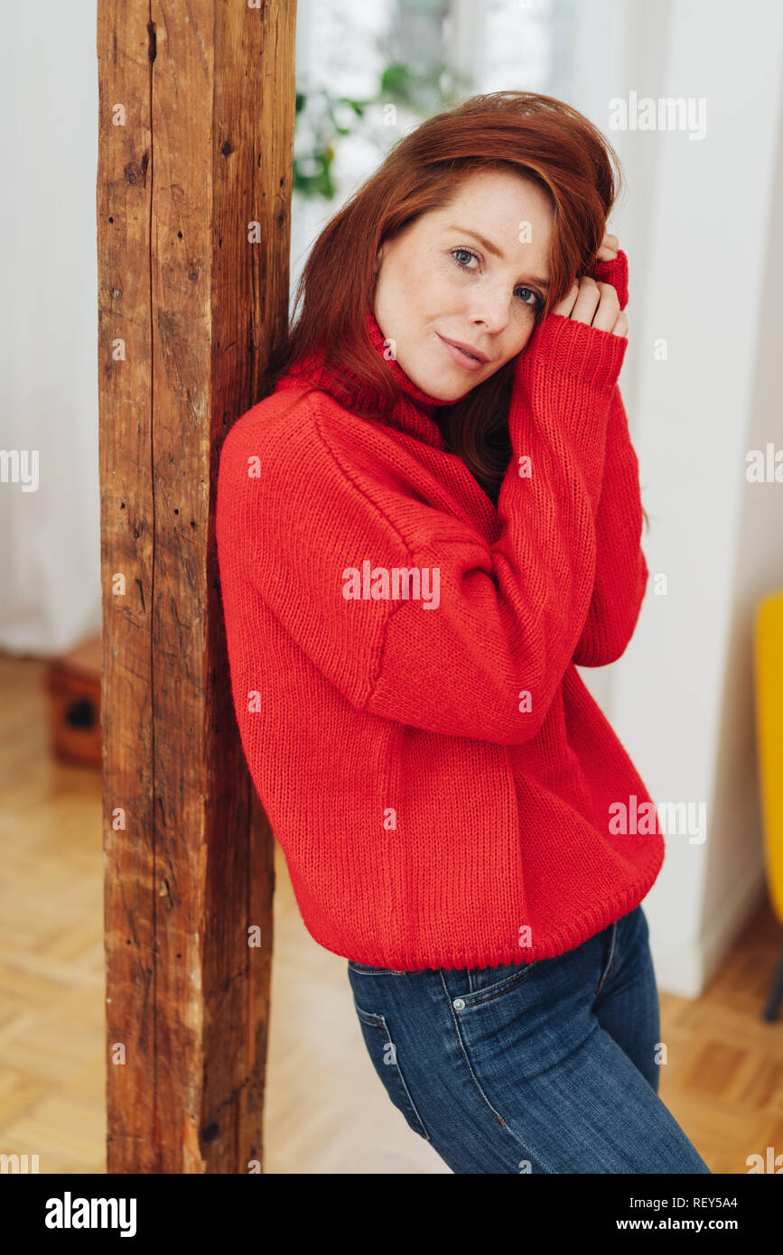 Thoughtful introvert young woman with long red hair standing leaning against a wooden pillar indoors looking at camera - Stock Image