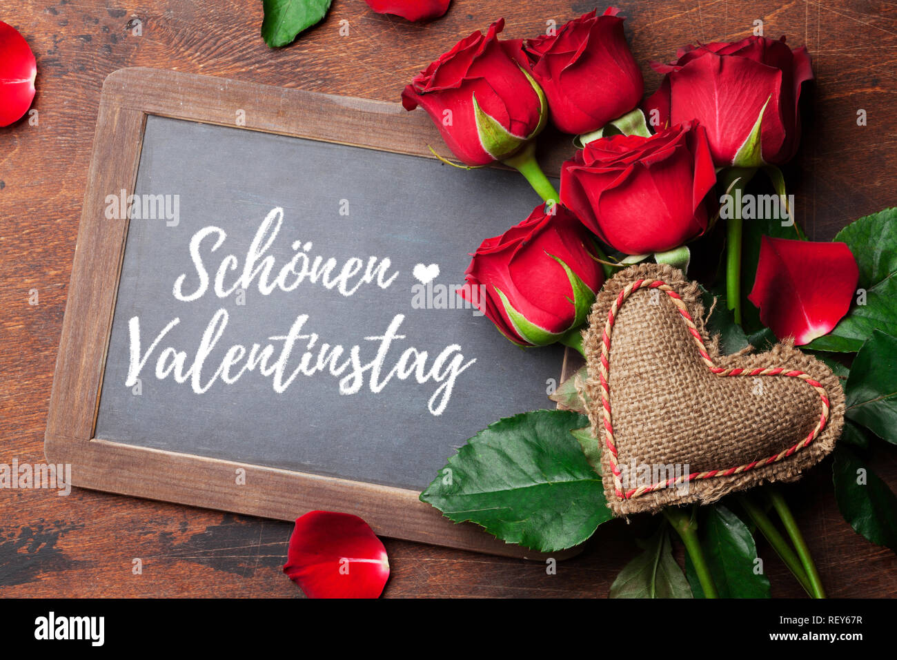 Valentine's day greeting card with red rose flowers bouquet on wooden background. Schönen Valentinstag Germany. Top view with chalkboard for your gree - Stock Image