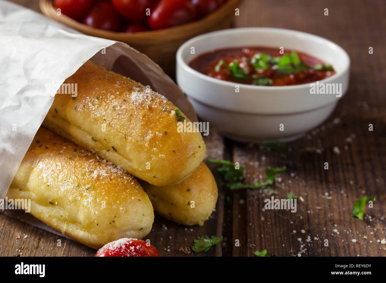 Close up of garlic bread sticks with marinara sauce on rustic wooden background, selective focus Stock Photo