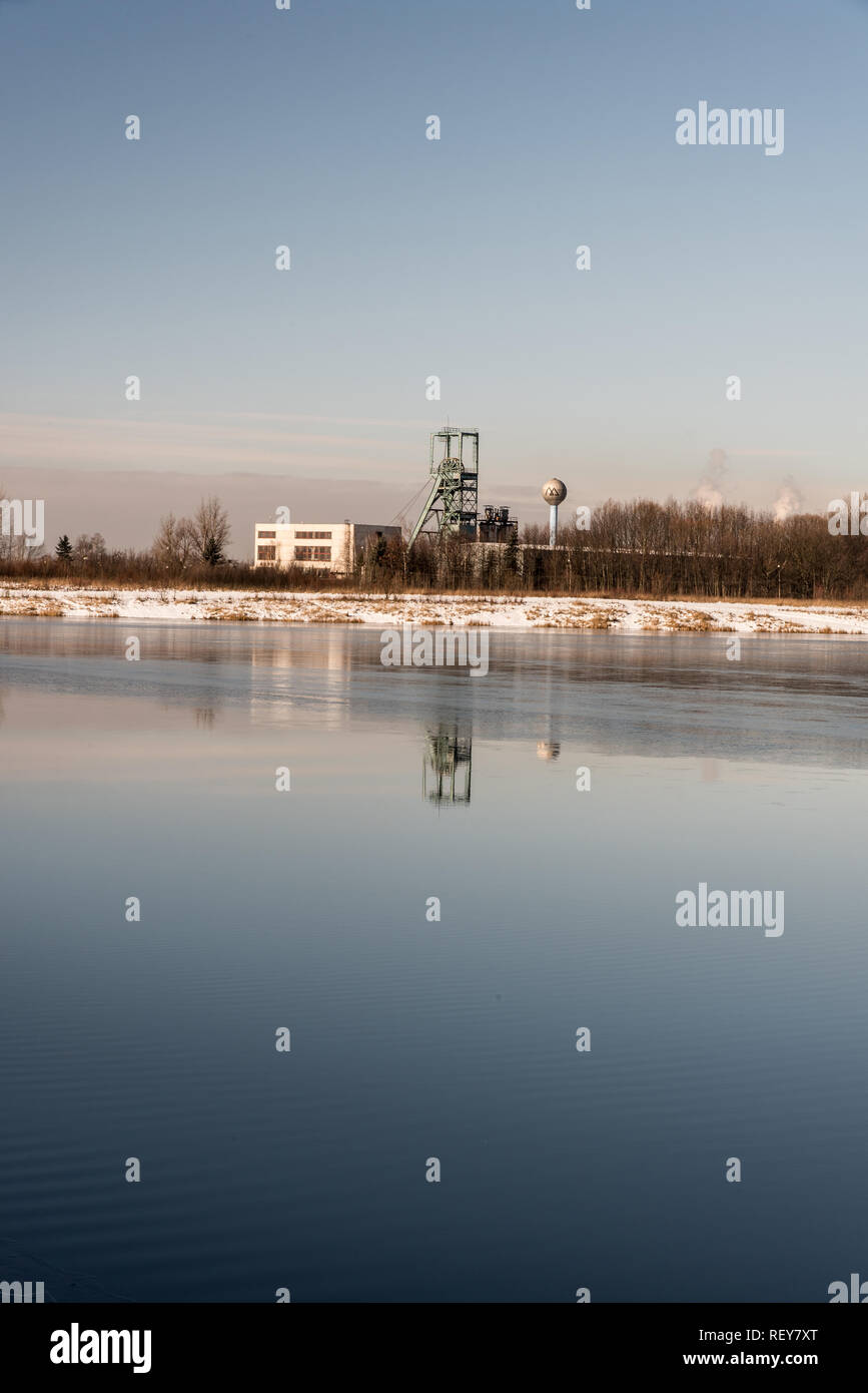 headframe od Ful Darkov bituminous coal mine reflecting on water fround of Karvinske more lake near Karvina city in Czech republic during winter day w - Stock Image