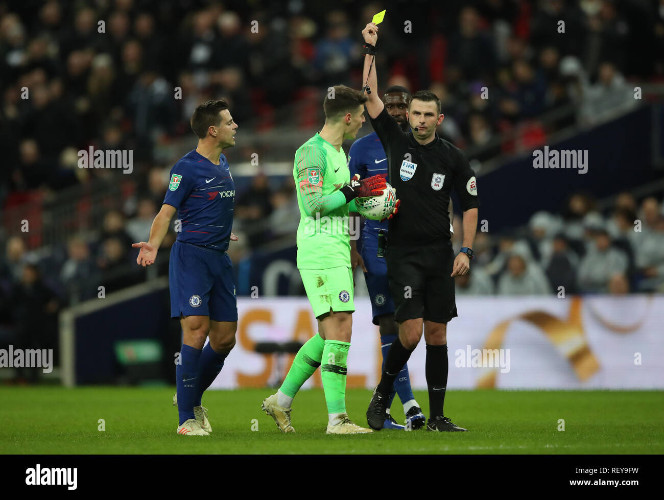 Chelsea goalkeeper Kepa Arrizabalaga is booked by referee Michael Oliver after foul on Tottenham Hotspur's Harry Kane who earned a penalty during the Carabao Cup, semi final match at Wembley, London. - Stock Image