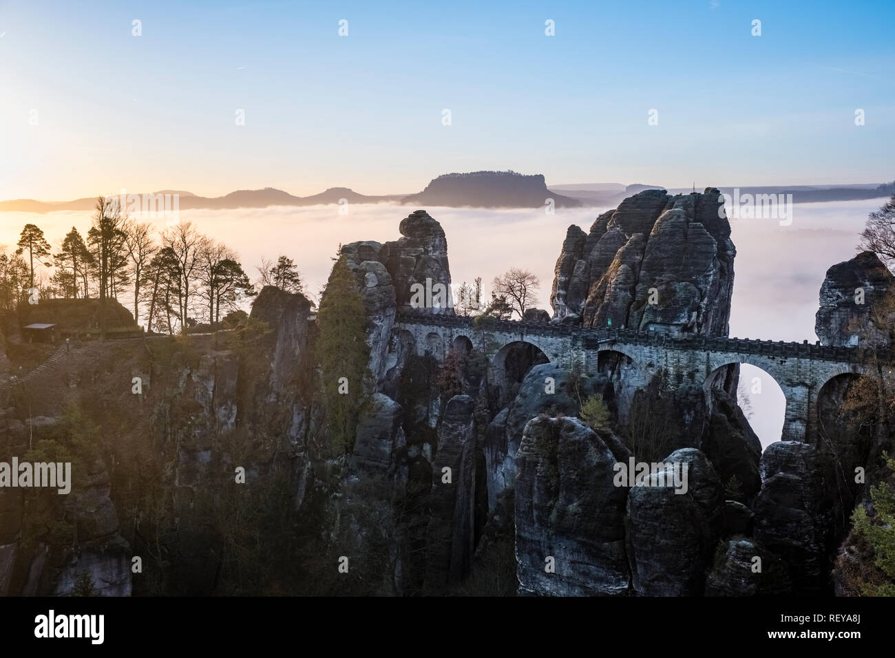 Landscape in the National Park Sächsische Schweiz with rock formations, Bastei bridge and trees, fog in the river Elbe valley at sunrise - Stock Image