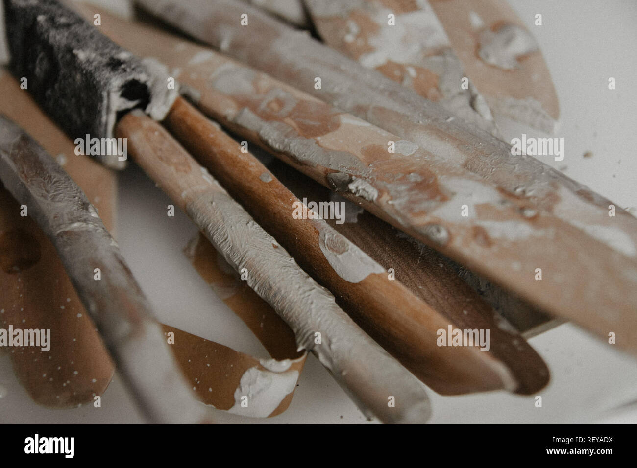 Set of dirty art and craft sculpting tools on wooden table in pottery workshop - Stock Image