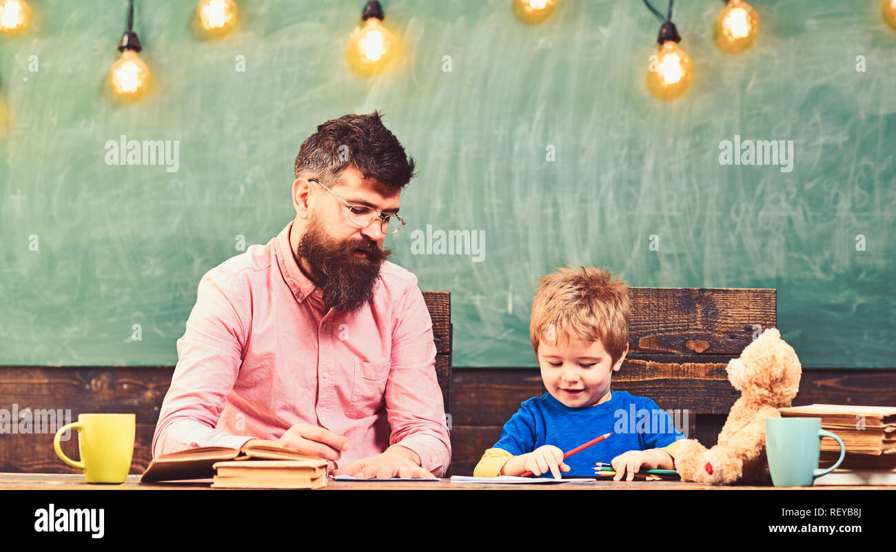 Teacher and small kid writing letters in copybook. Cute boy drawing a picture with colorful pencils. Art lesson at kindergarten Stock Photo