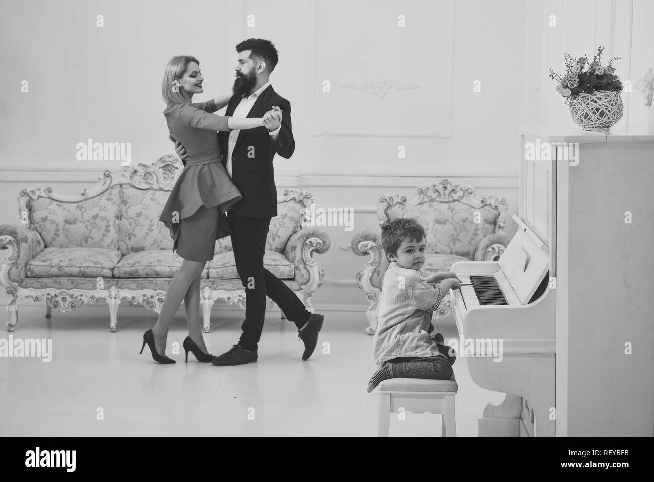 Rich parents enjoy parenthood. Boy adorable try to play piano musical instrument, while parents dancing. Child sit next to piano, play music, white interior background. Musician education concept. - Stock Image