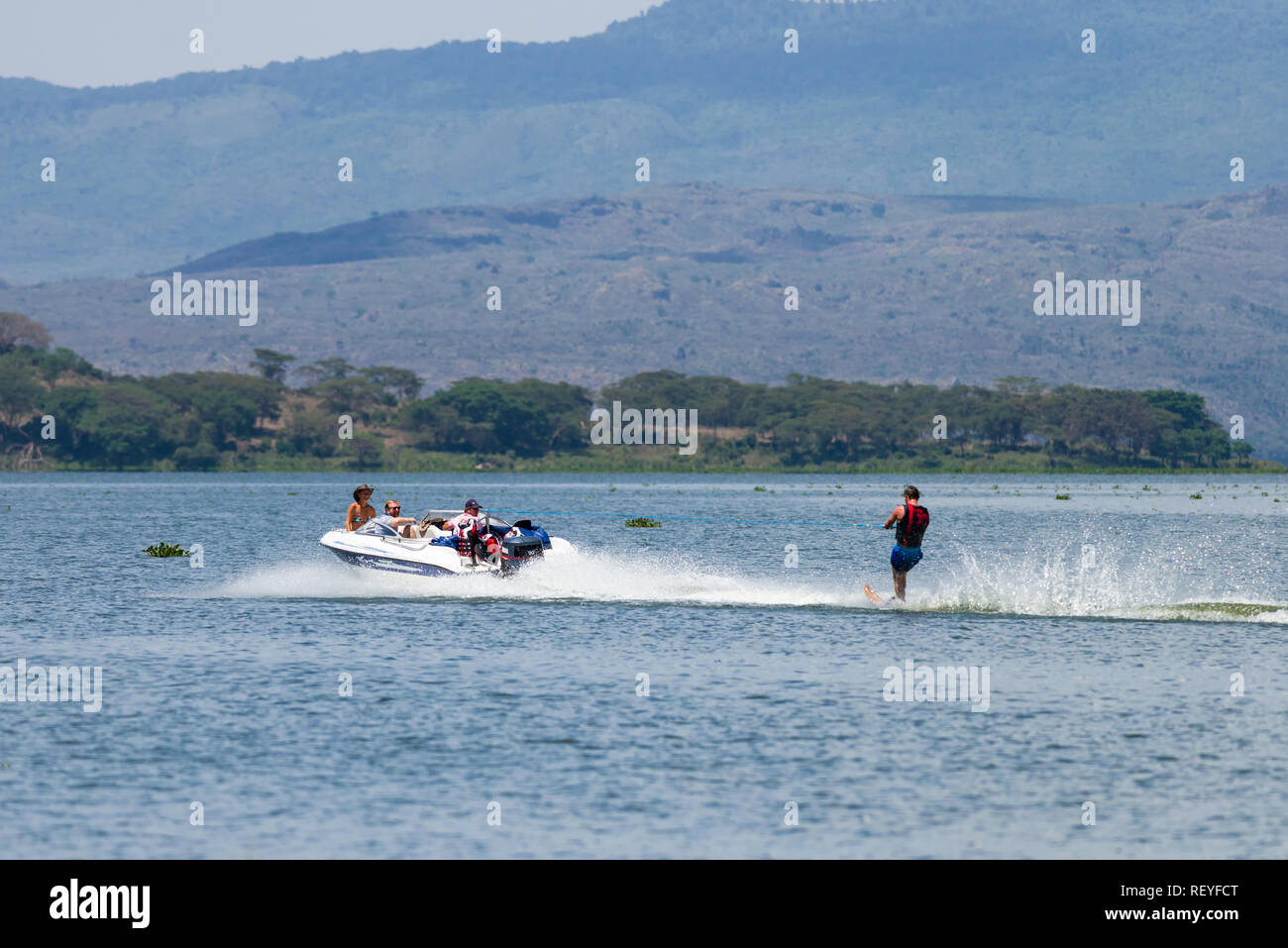 A Caucasian man wakeboarding behind a powerboat as passengers watch him, Lake Naivasha, Kenya - Stock Image