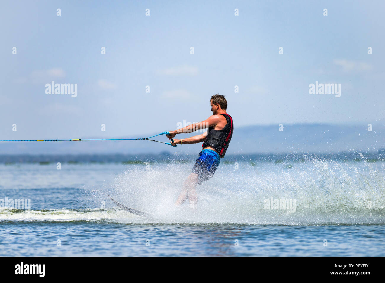 A Caucasian man wakeboarding with water spray behind him, Lake Naivasha, Kenya - Stock Image