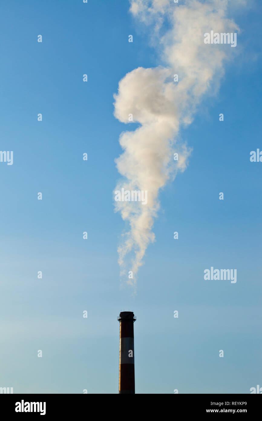 A smoke stack discharging smoke or steam in south Seattle, Washington,  USA - Stock Image