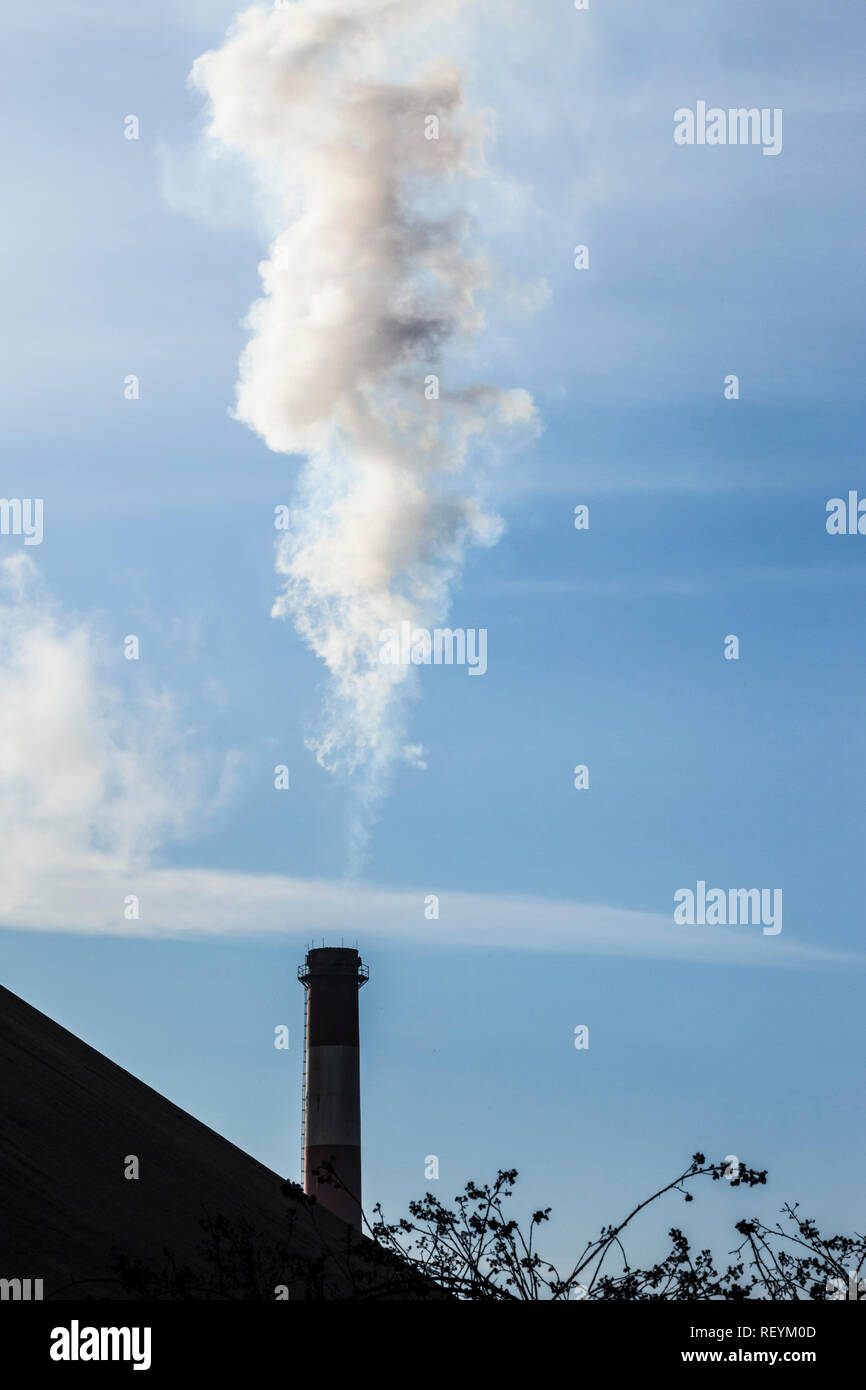 A smoke stack discharging smoke or steam in south Seattle, Washington,  USA - Stock Image