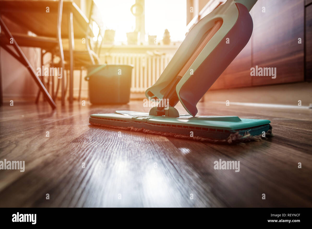 Wiping dirty wooden floor by wet wiper mop, housework - Stock Image