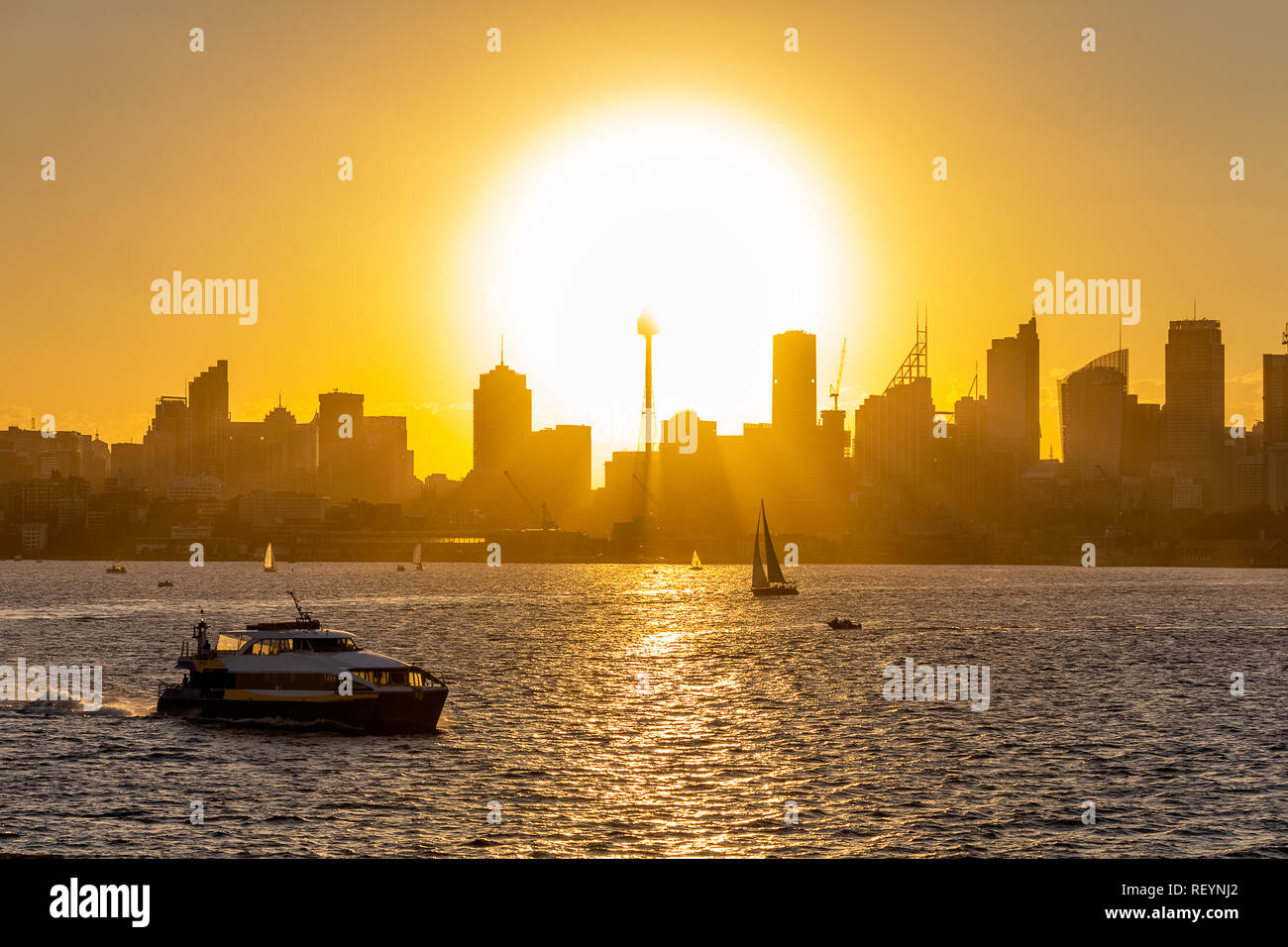View of downtown Sydney at sunset with Sun disk setting down behind buildings a boat sailing in the foreground - Stock Image