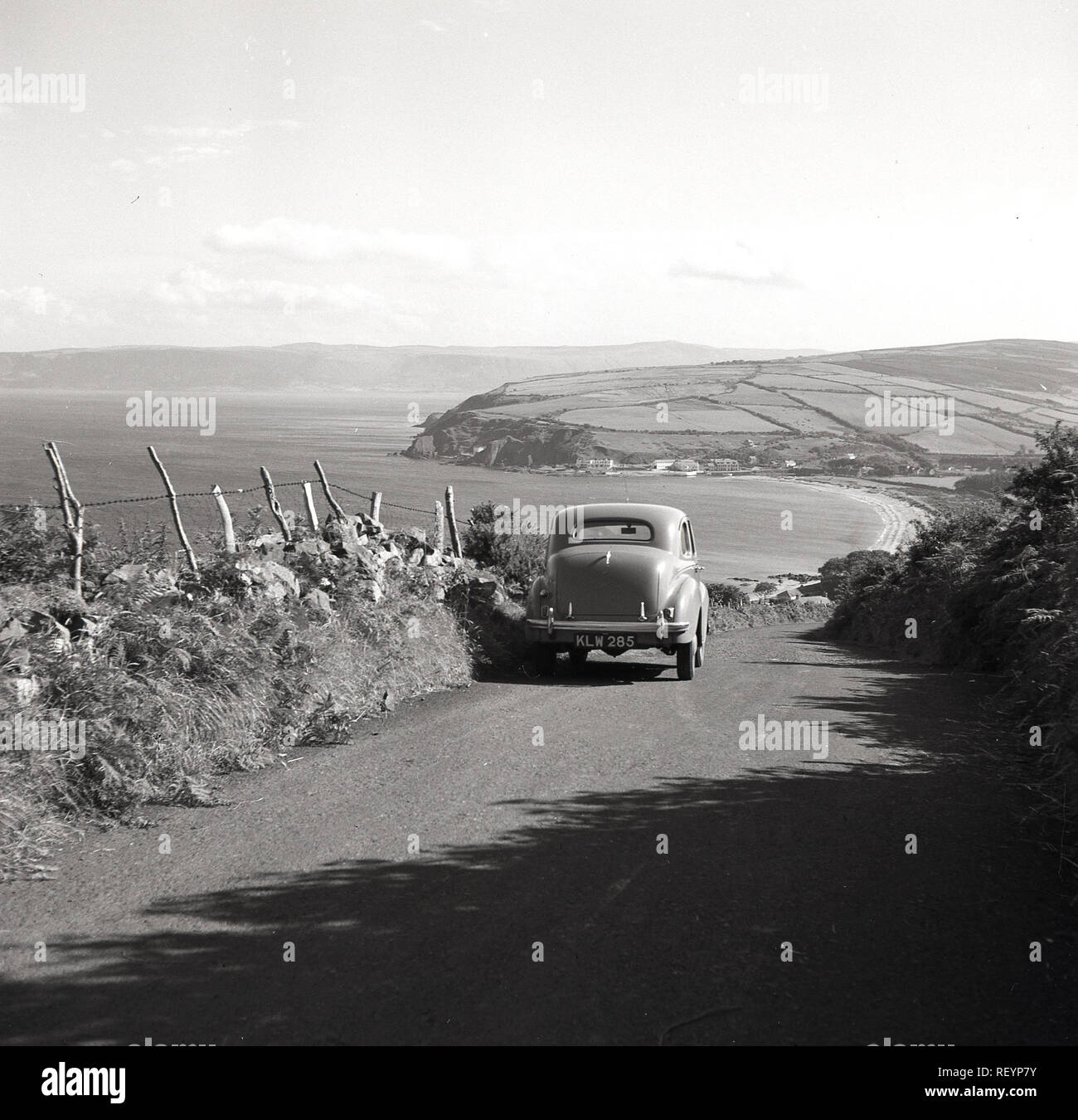 1950s, historical, an Austin car of the era parked on the hillside on a country lane in Co. Antrim overlooking the Atlantic ocean in Northern Ireland. Antrim is famous for its beautiful coastal road, the Causeway Coastal Route Stock Photo