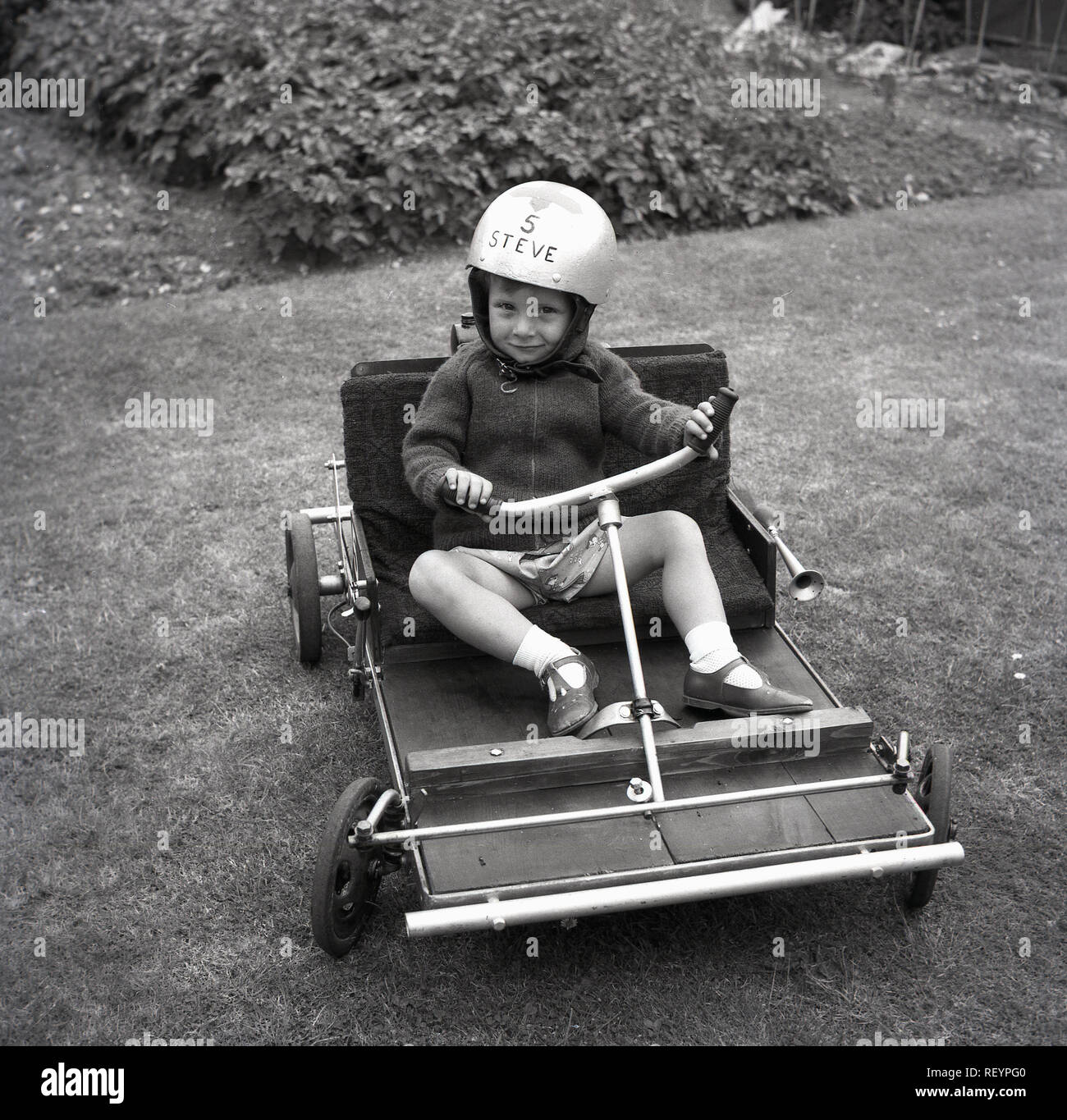 1967, historical, young boy in a back garden sitting in a
