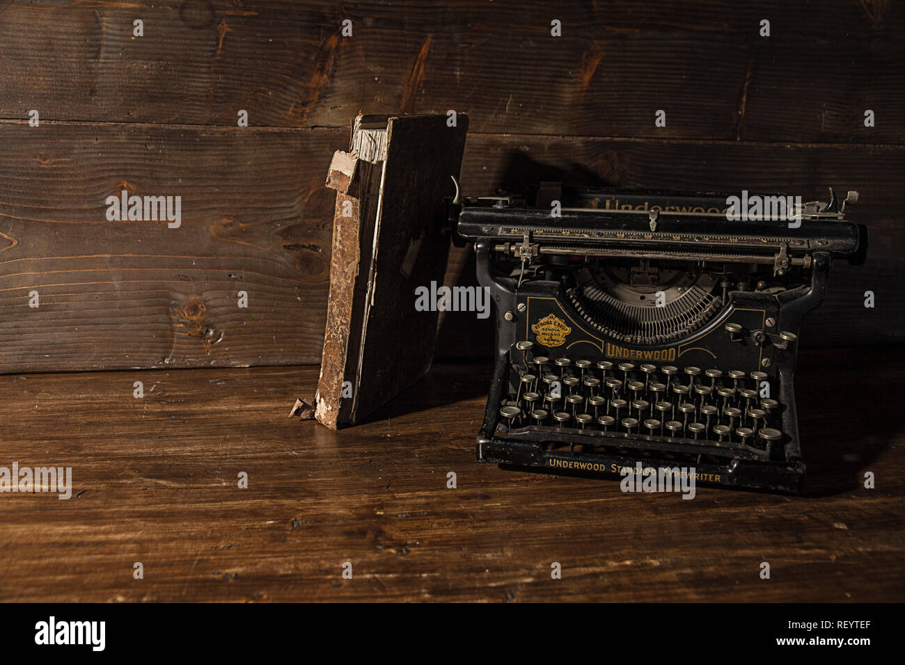 Reading and writing scenes in ancient times: an old book and an old typewriter on a ruined wooden table  on a wooden background Stock Photo