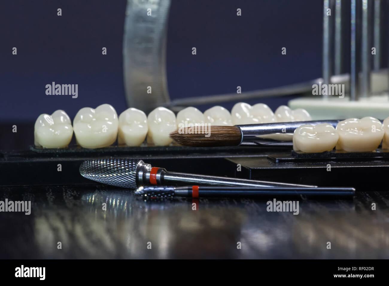 Acrylic teeth and dental instruments. Stomatologic instrument, close up view - Stock Image
