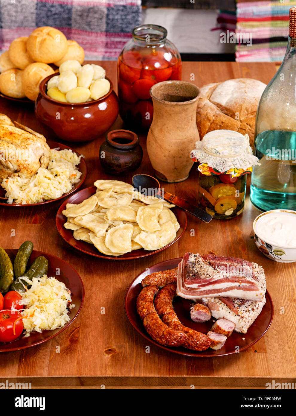 Fat, dumplings, canned tomatoes, cucumbers and cabbage, moonshine and boiled potatoes on the table - Stock Image