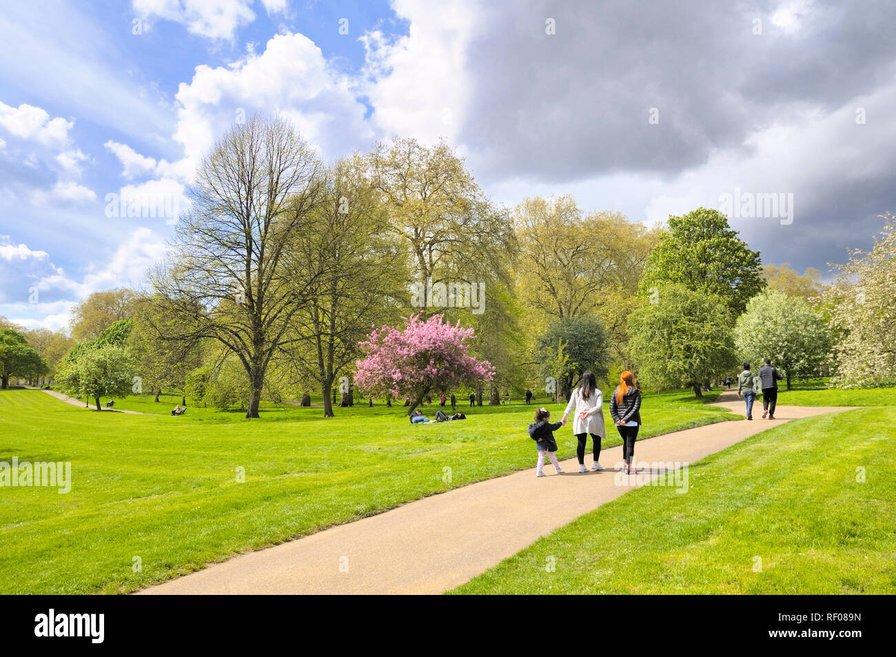 People strolling in Green Park on a fine spring day, London, England, UK - Stock Image