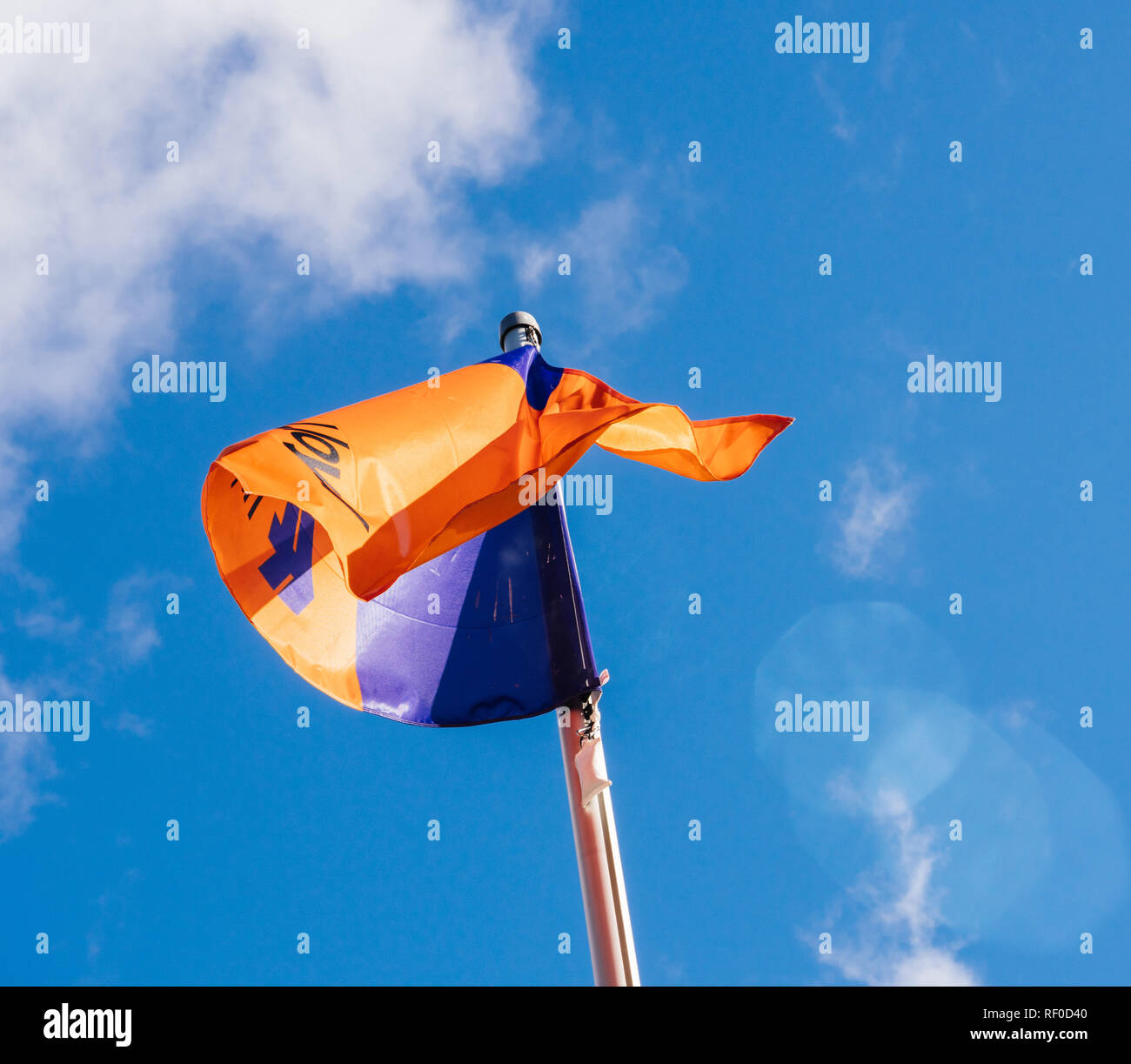 HAMBURG, GERMANY - MAR 20, 2018: Waving Hapag-Lloyd transnational German-based transportation company flag against blue sky - Stock Image