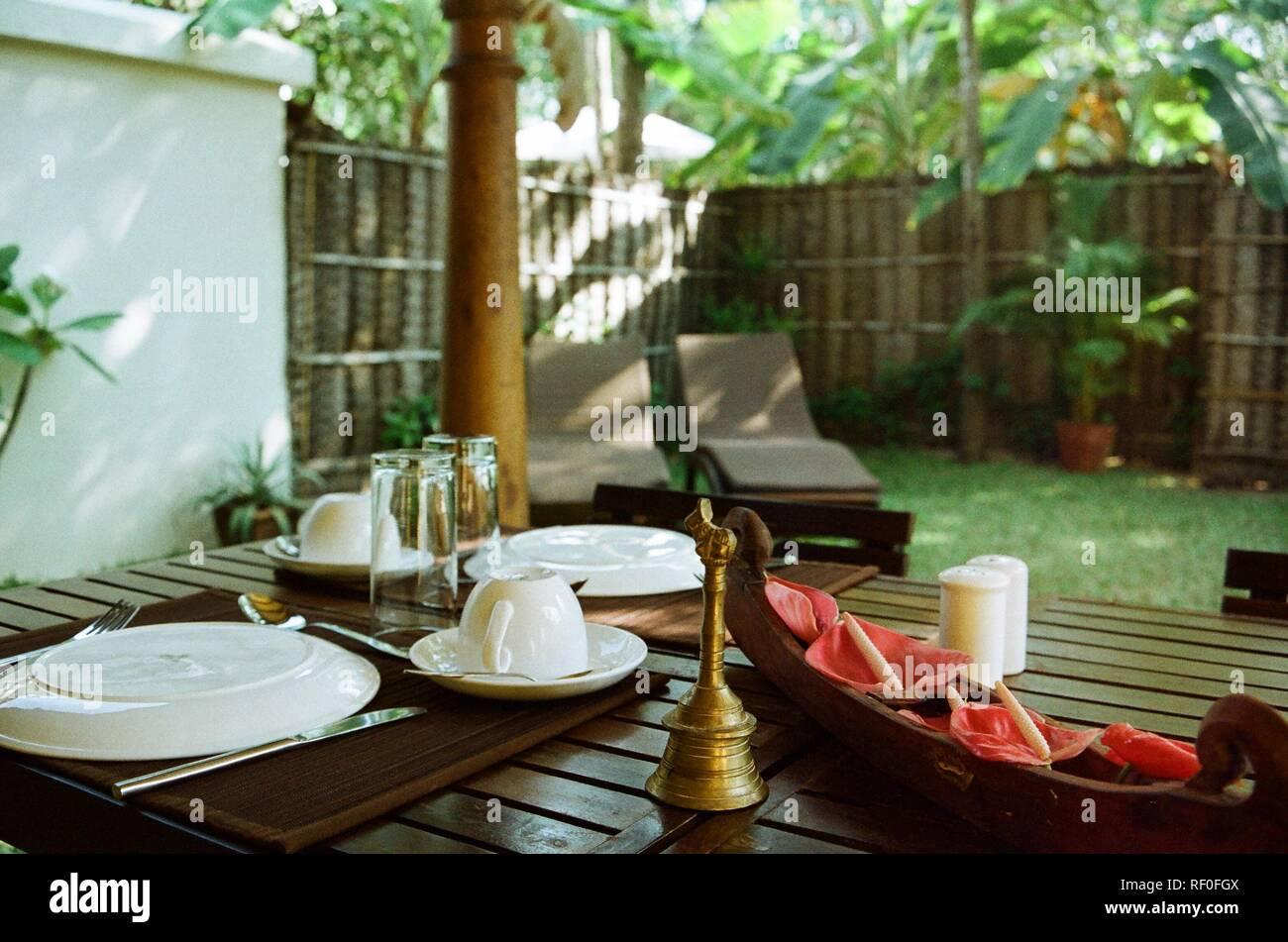 A freshly laid table with flowers and a brass bell in the private garden of a converted fisherman's house in Alappuzha, Kerala, India. - Stock Image