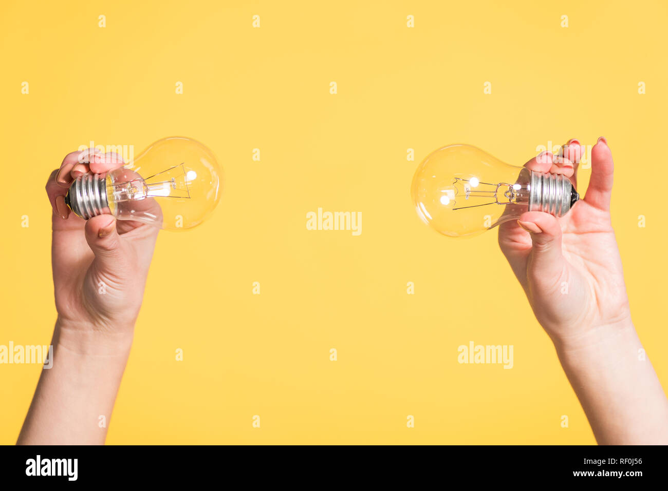 cropped view of female hands holding led lamps isolated on yellow, energy efficiency concept - Stock Image