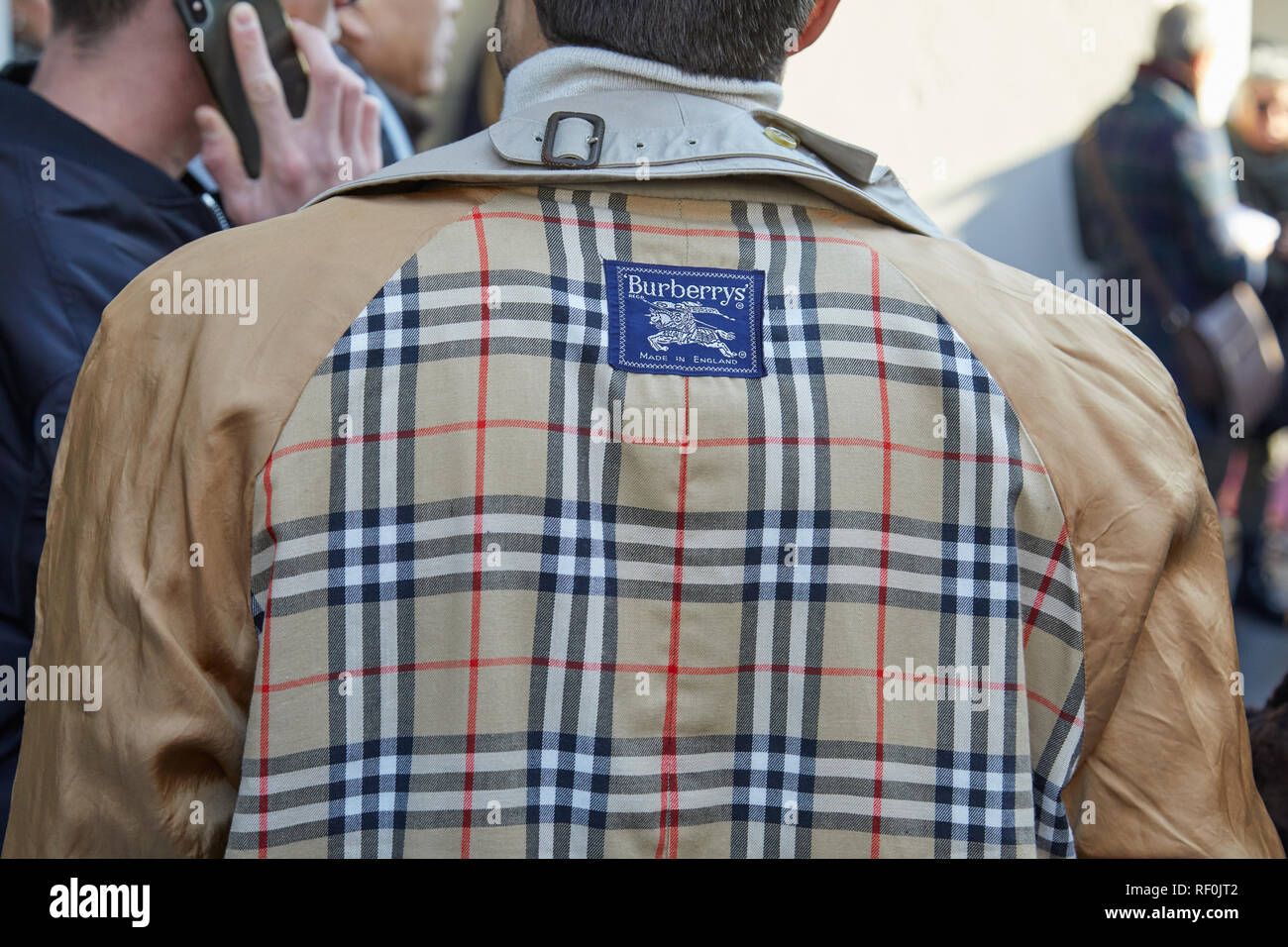 MILAN, ITALY - JANUARY 13, 2019: Man with beige Burberry trench coat before John Richmond fashion show, Milan Fashion Week street style - Stock Image