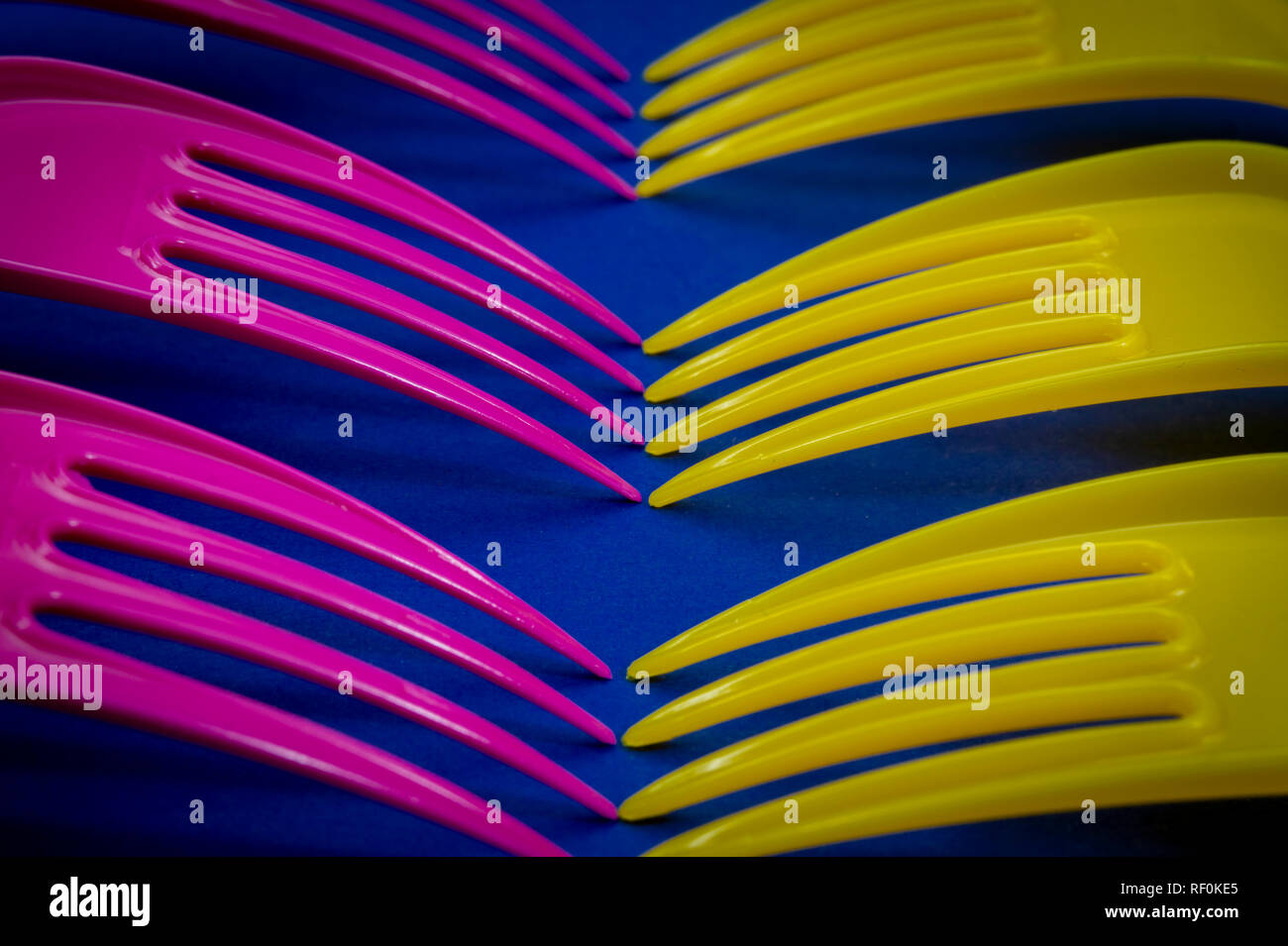 Yellow and pink cutlery plastic forks arranged on blue background. Color trends and plastic waste problem concept Stock Photo