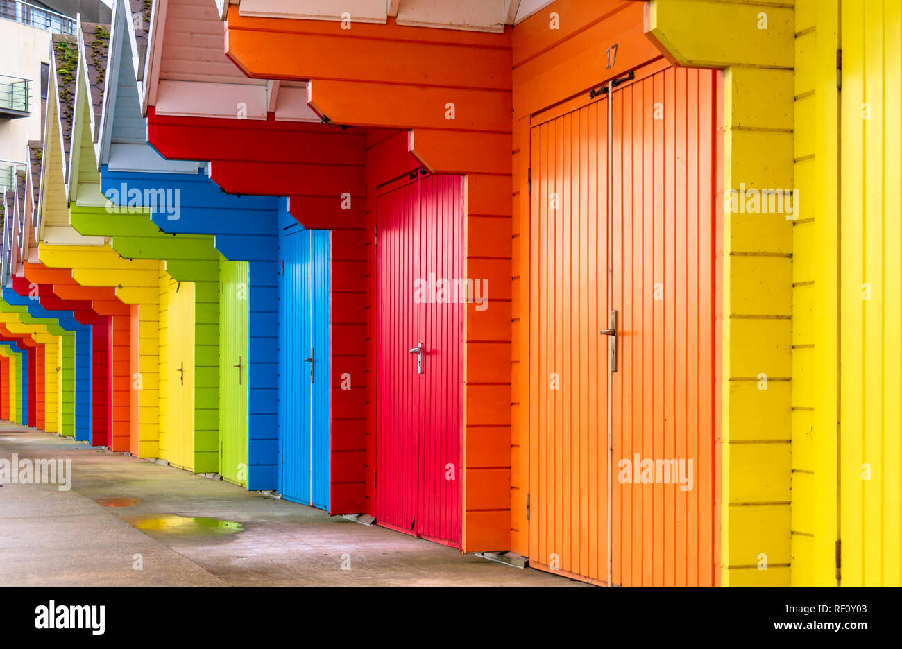 A line of coloured beach huts. A building with a balcony lies beyond and there is a puddle on the concrete floor. - Stock Image