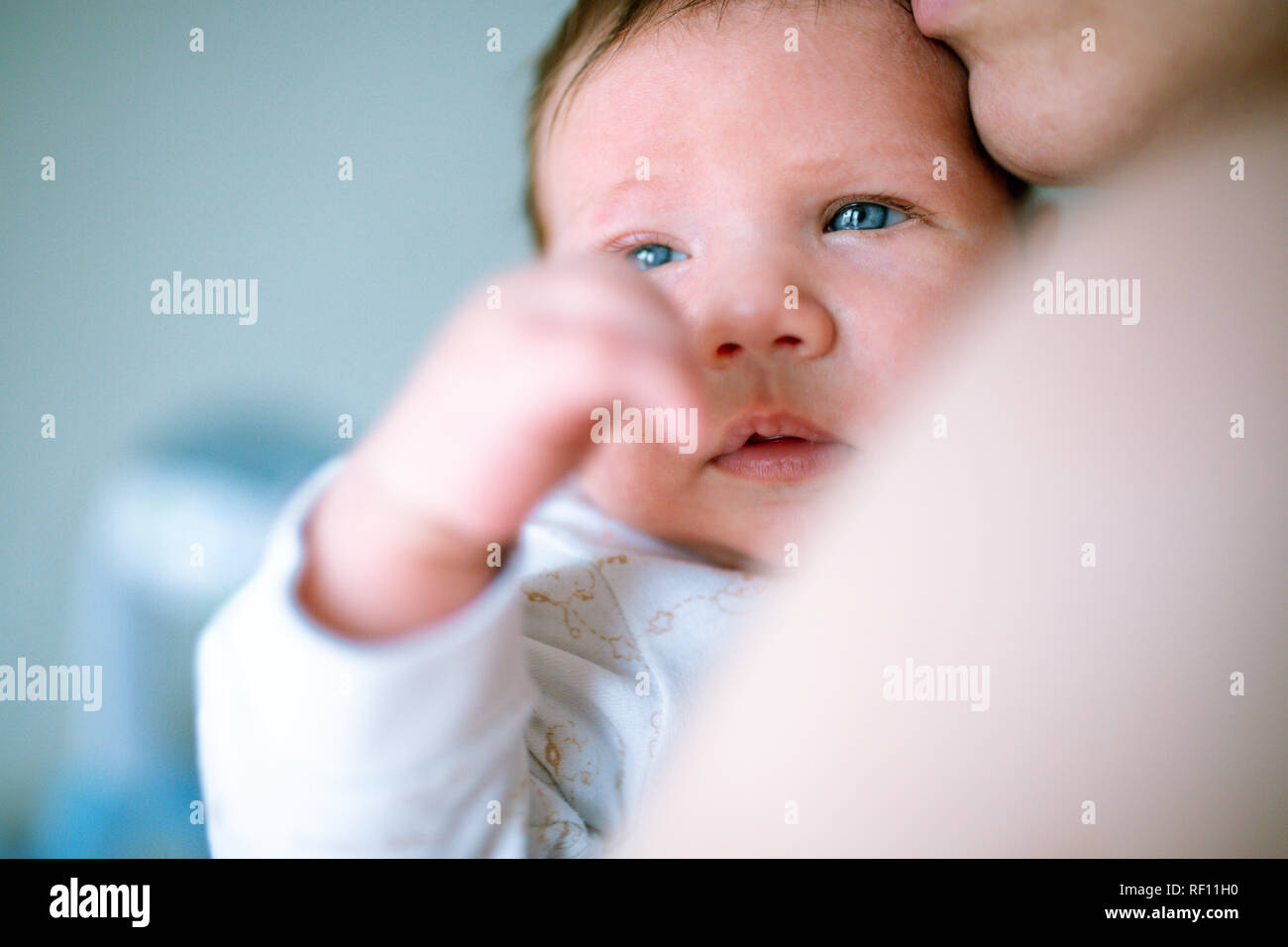 Young mother hugging her newborn child. Mom nursing baby. Family at home. Love, trust and tenderness concept. Stock Photo