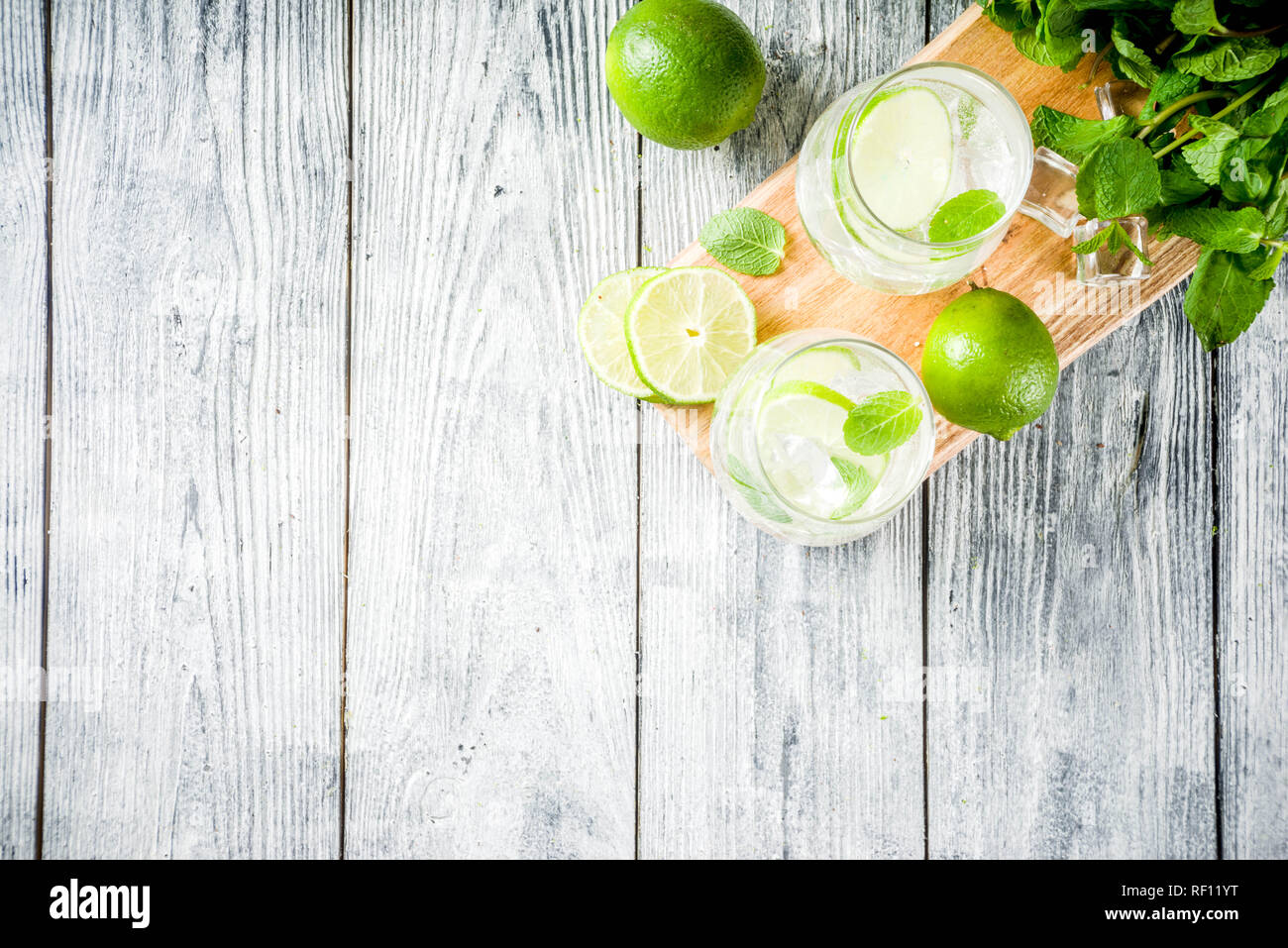 Summer sour drink, with lime and mint, homemade cocktail mojito in two glasses, white wooden background, with fresh limes, mint leaves, ice cubes, cop - Stock Image