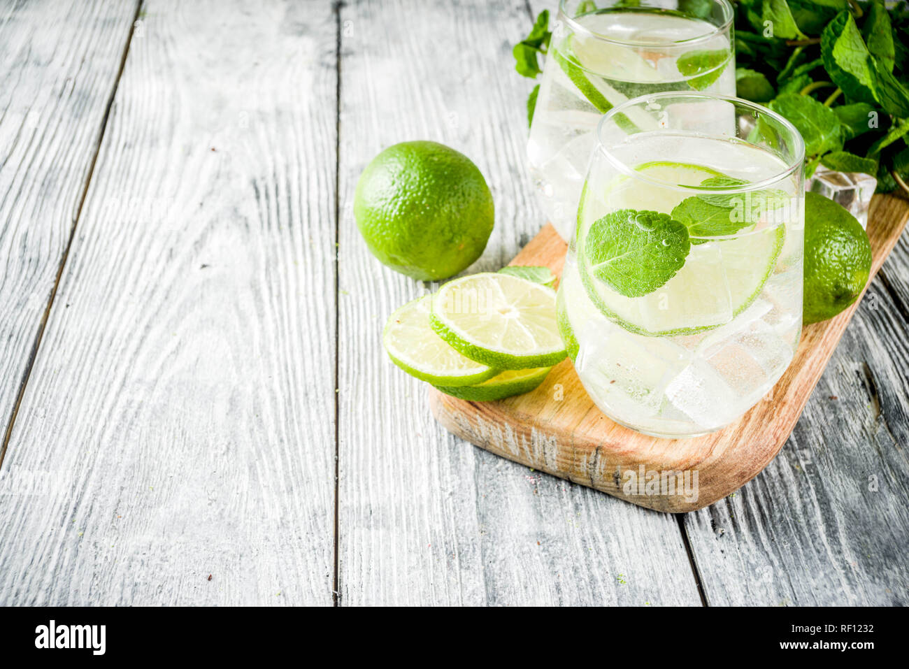 Summer sour drink, with lime and mint, homemade cocktail mojito in two glasses, white wooden background, with fresh limes, mint leaves, ice cubes, cop Stock Photo