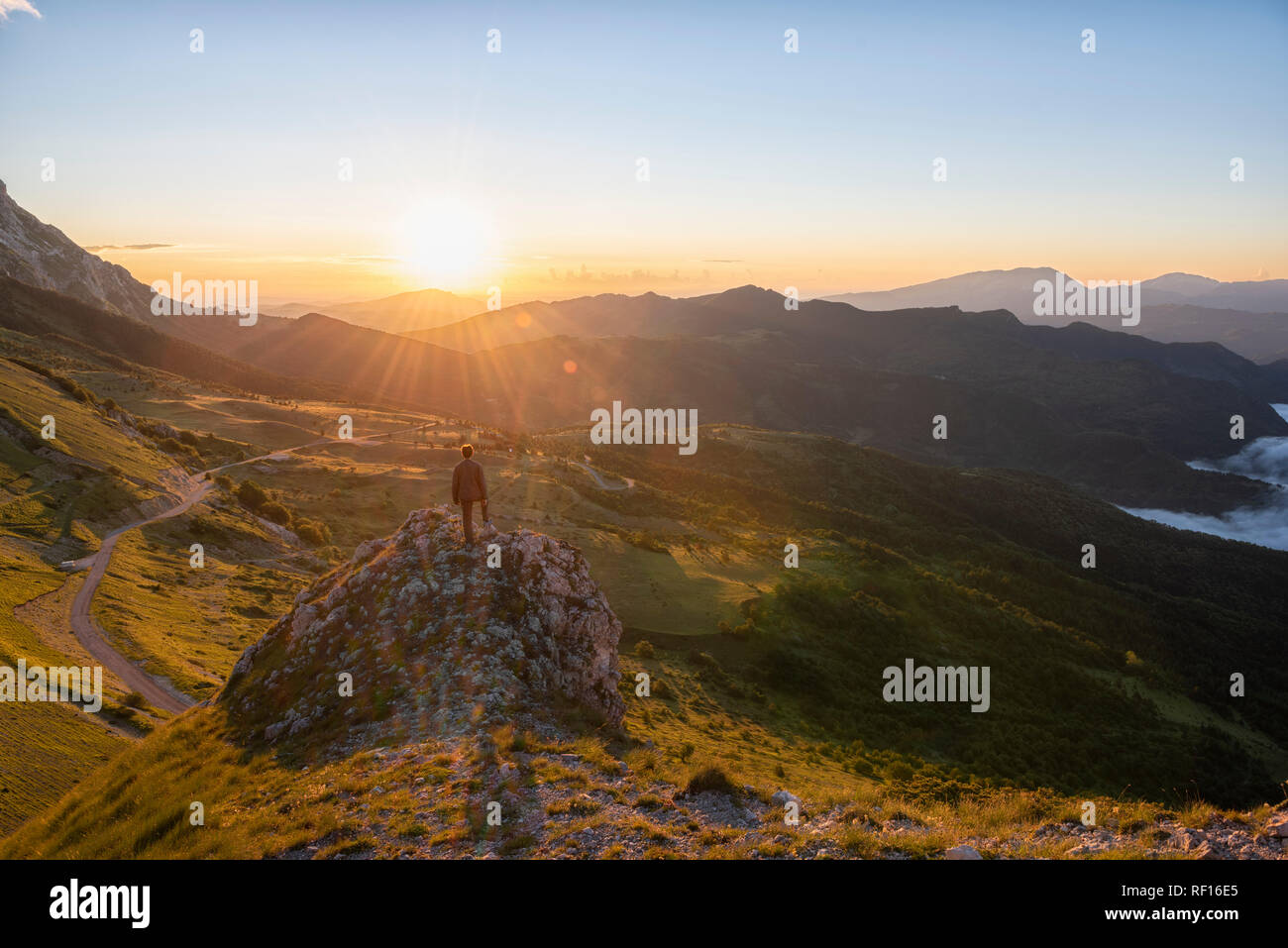 Italy, Umbria, Sibillini National Park, hiker standing on viewpoint at sunrise - Stock Image