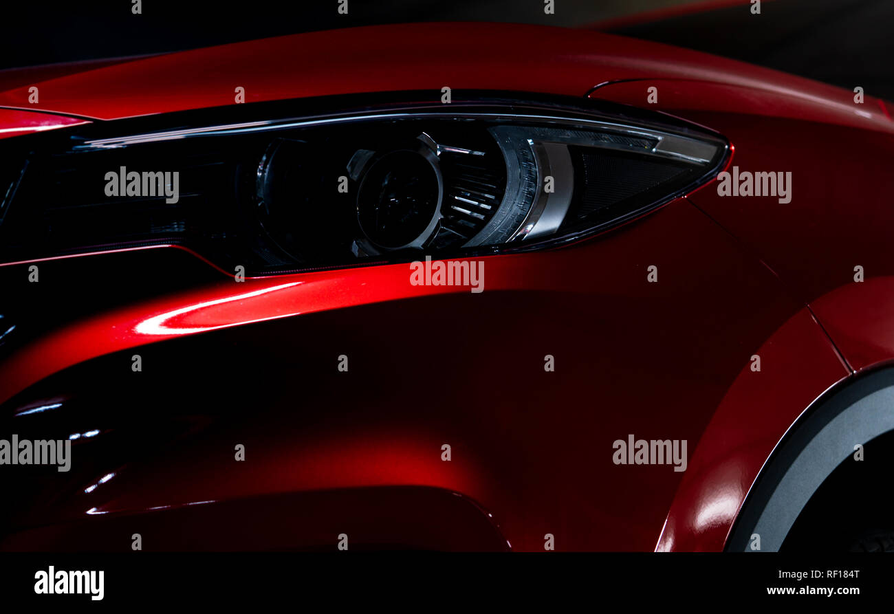 Closeup headlight of shiny red luxury SUV compact car. Elegant electric car technology and business concept. Hybrid auto and automotive concept. Car - Stock Image