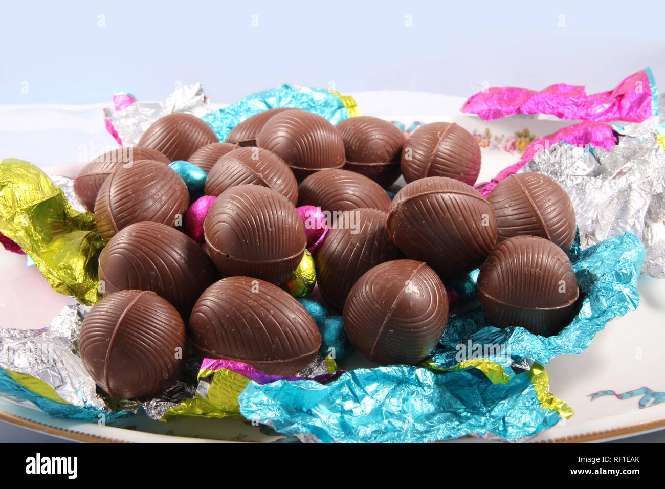 Pile of unwrapped chocolate easter eggs with the colourful foil wrapping surrounding it on a white background. - Stock Image