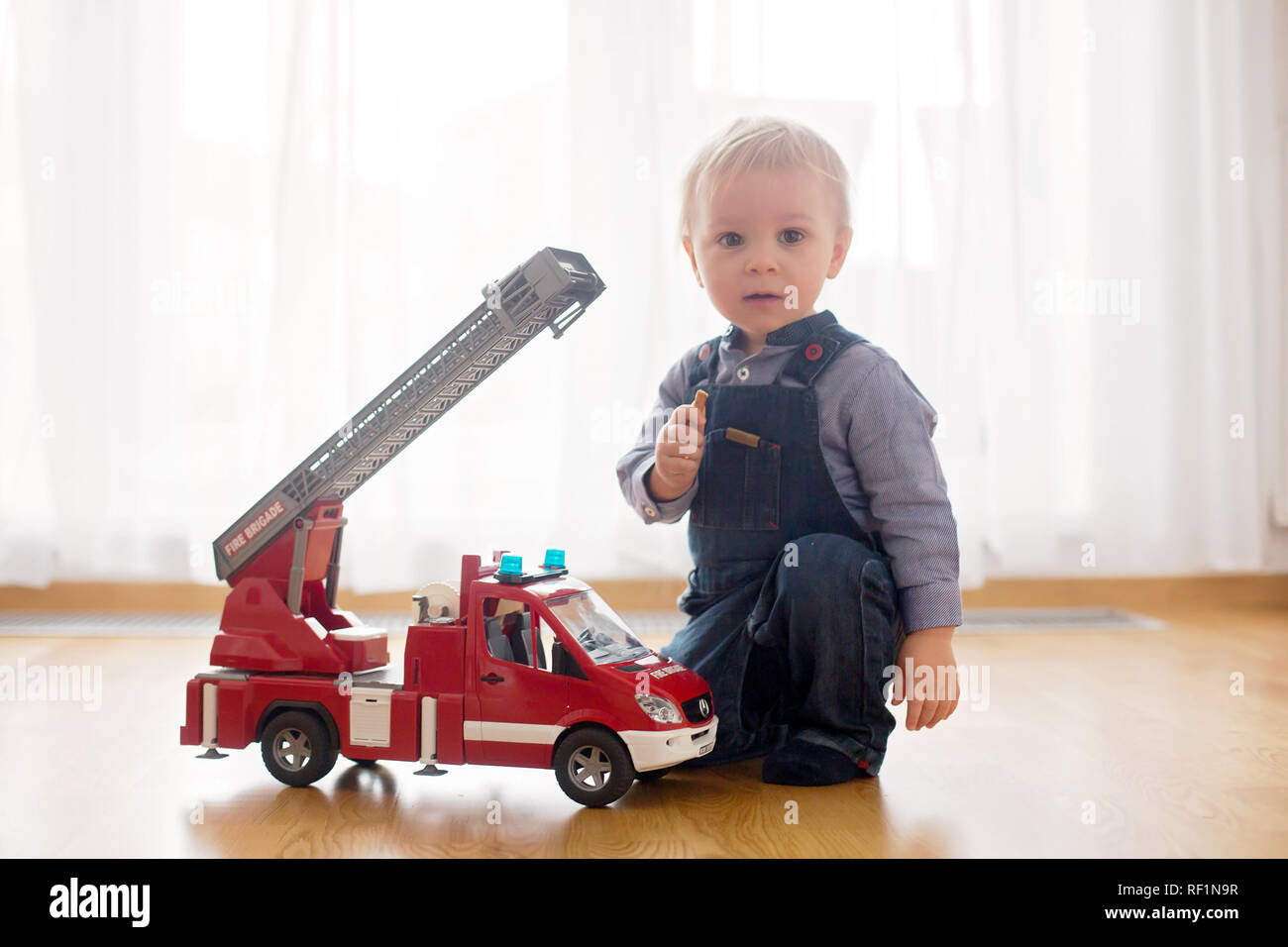Little Toddler Boy Playing With Fire Truck Car Toy At Home