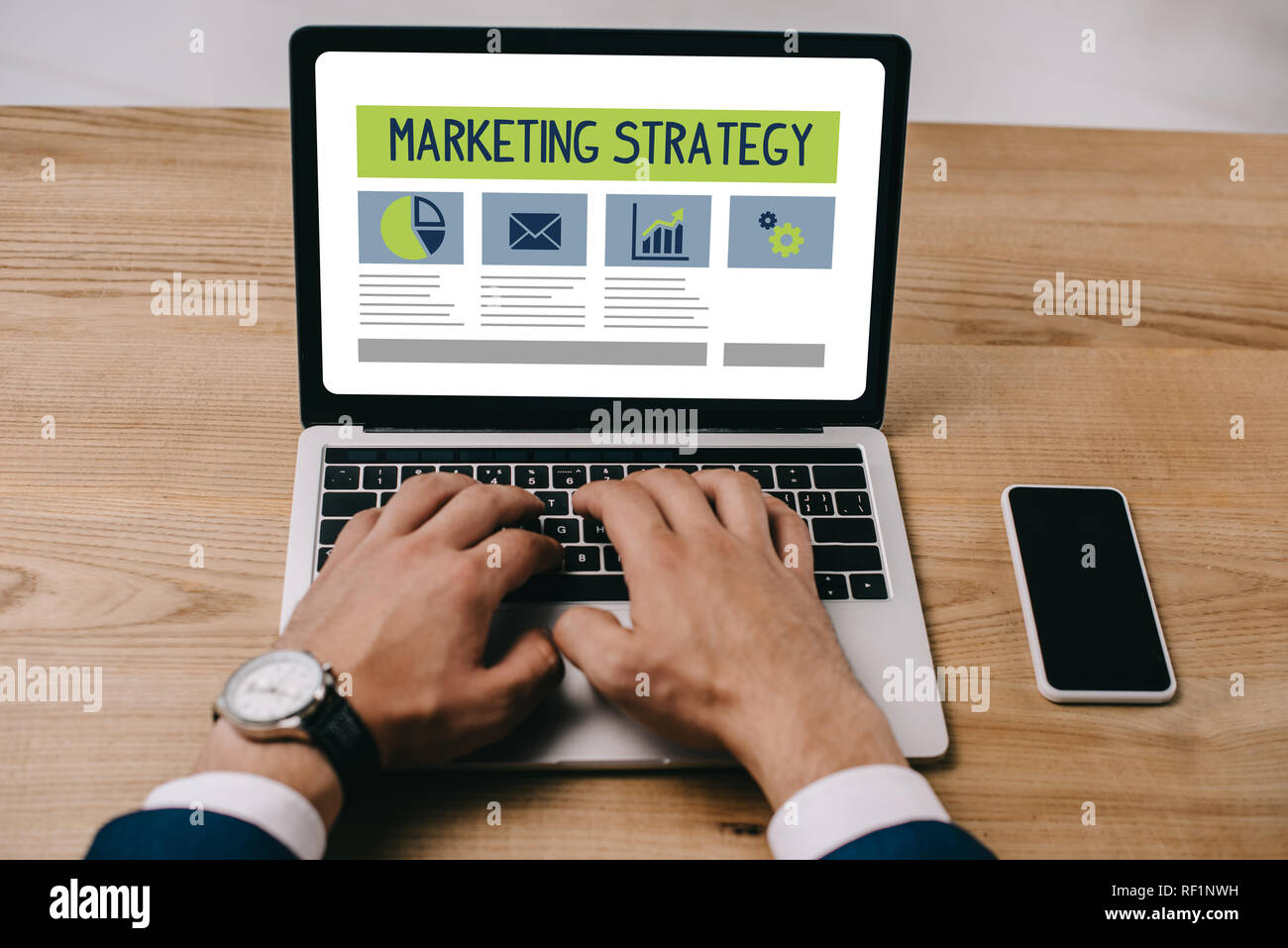cropped view of businessman typing on laptop with marketing strategy icons - Stock Image